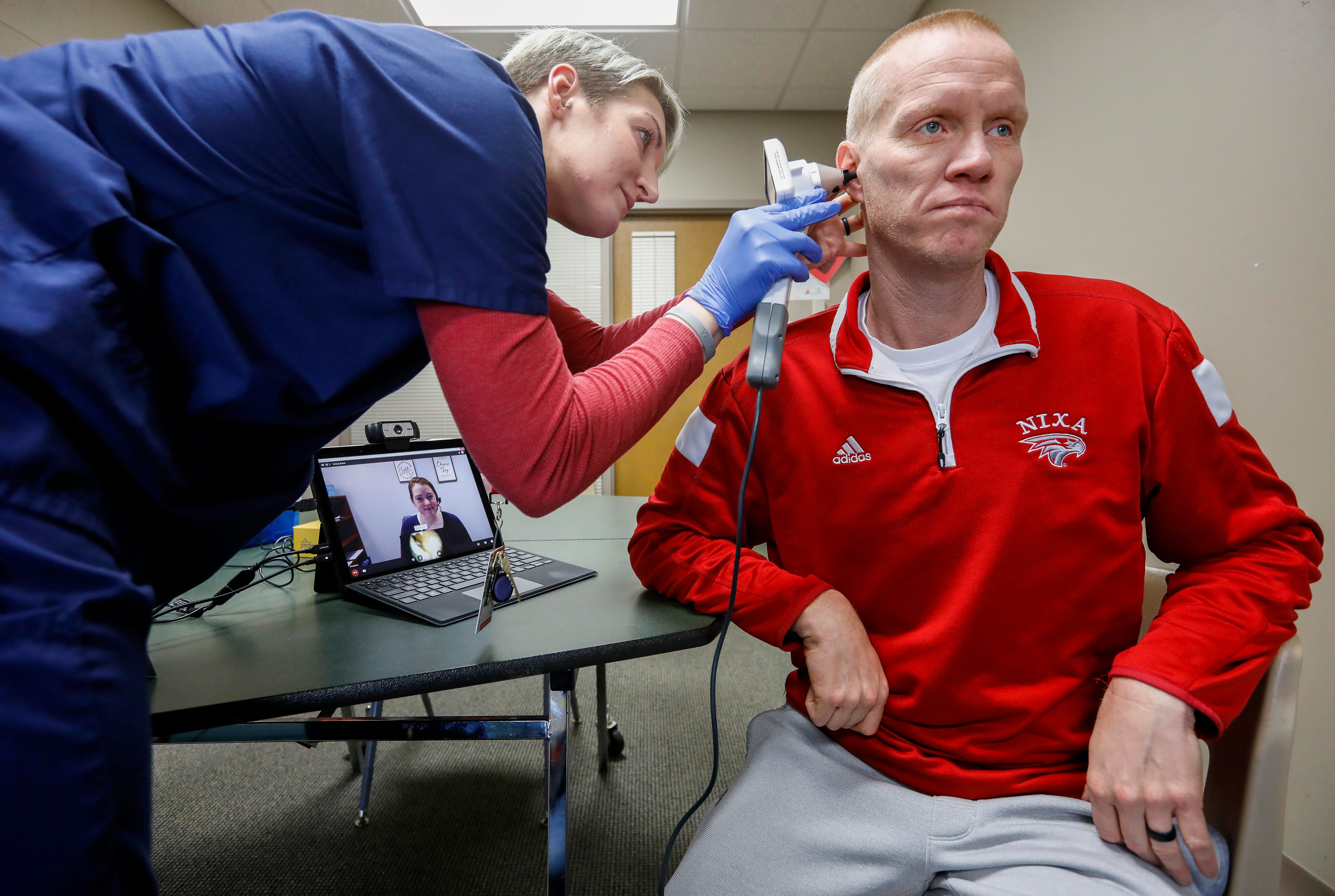 Kristen Hook, a clinic navigator, uses a otoscope lens to look in physical education teacher Brock Blansit's ear at the Cox Health clinic inside of Nixa High School.