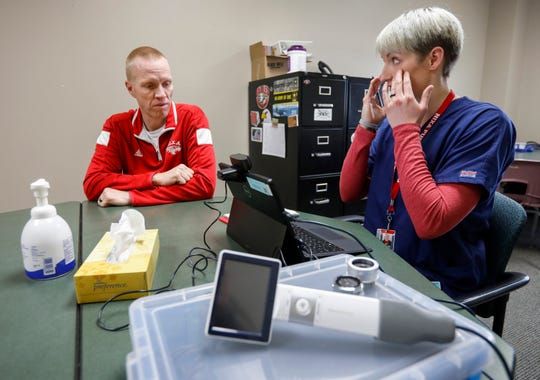 Kristen Hook, a clinic navigator, talks with physical education teacher Brock Blansit at the Cox Health clinic inside of Nixa High School.