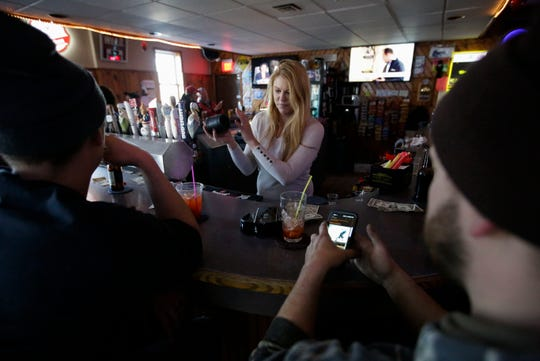 "Bartender Lynn Schneider plays a game of ""Farmers,"" a pub dice game, with patrons on Feb. 15 at Jacks in Marshfield."
