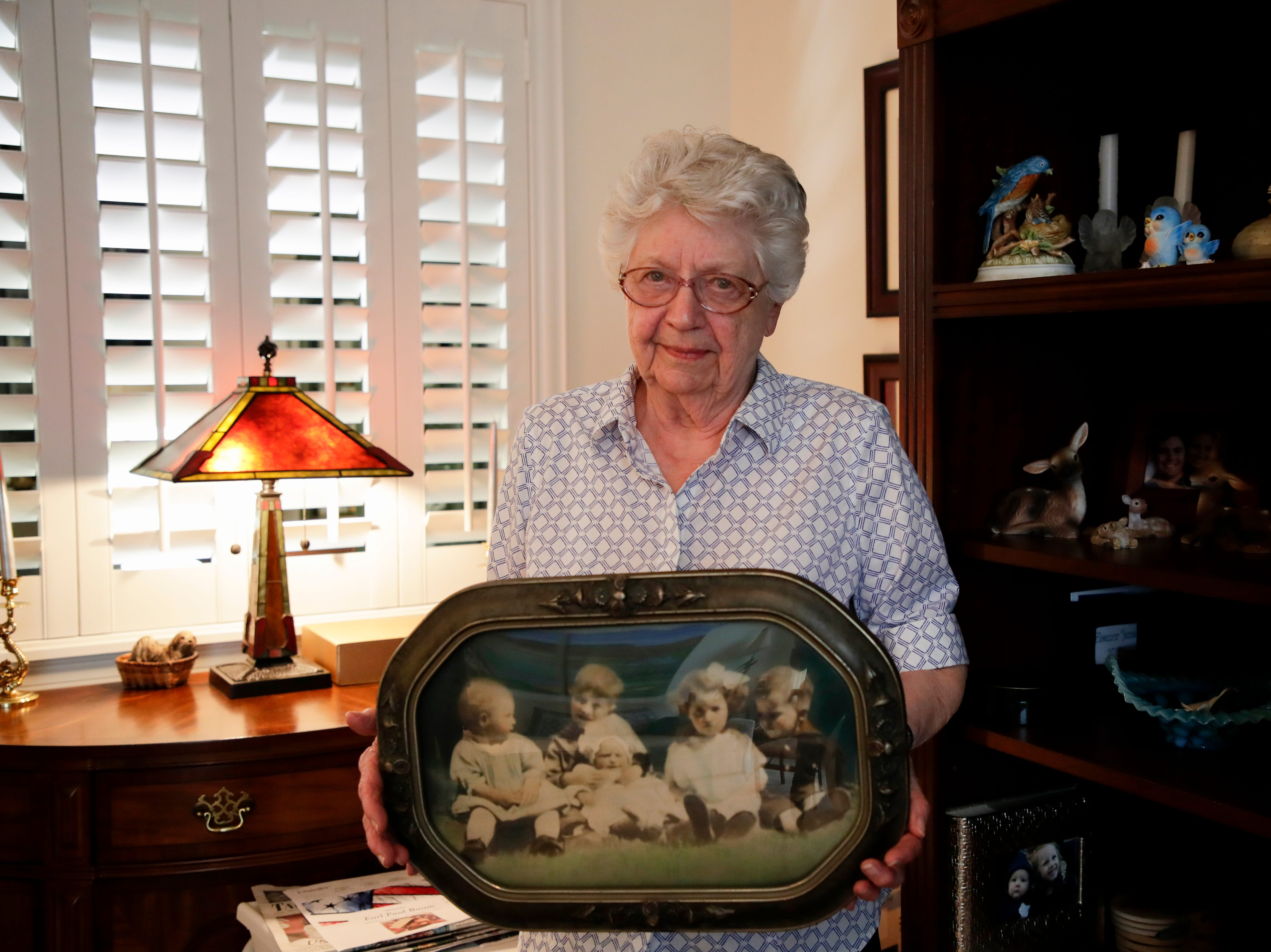 Emily Golz holds a photo from her childhood showing her and her siblings. In the photo she, the youngest, is being held in the lap of her oldest brother Earl Baum, who died at Pearl Harbor in 1941. Baum's remains were identified last year through DNA. He will be buried March 8, 2019 at Tallahassee National Cemetery.