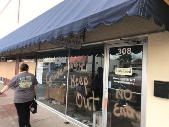 A passerby views the damage to the interior of the Gulf County Chamber of Commerce storefront.