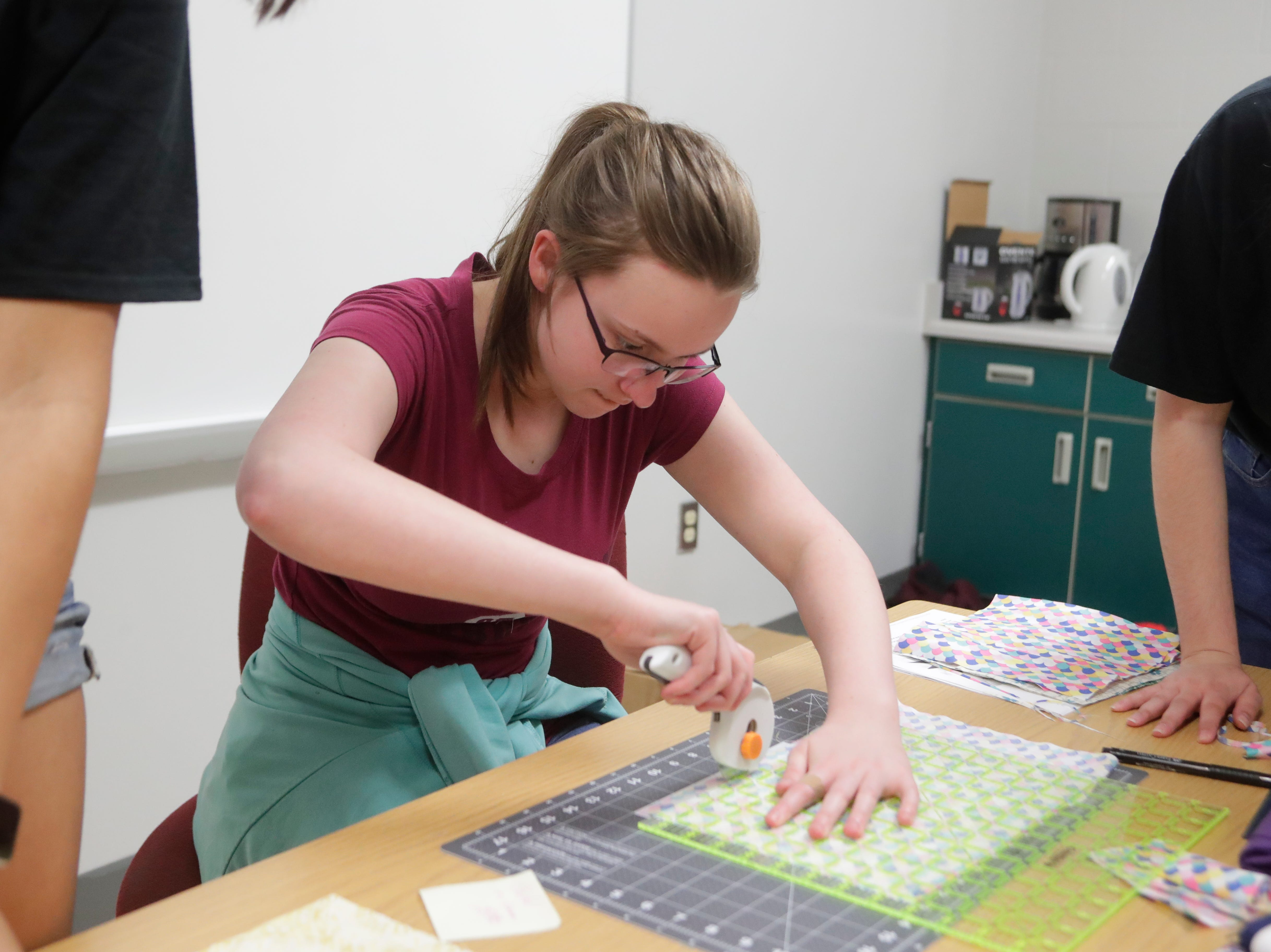 Autumn Kennedy, a sophomore at Chiles High School and member of the Chiles Sewing Club, cuts squares out of fabric to be sewn into quilts people at the refuge home, Thursday Feb. 21, 2019.