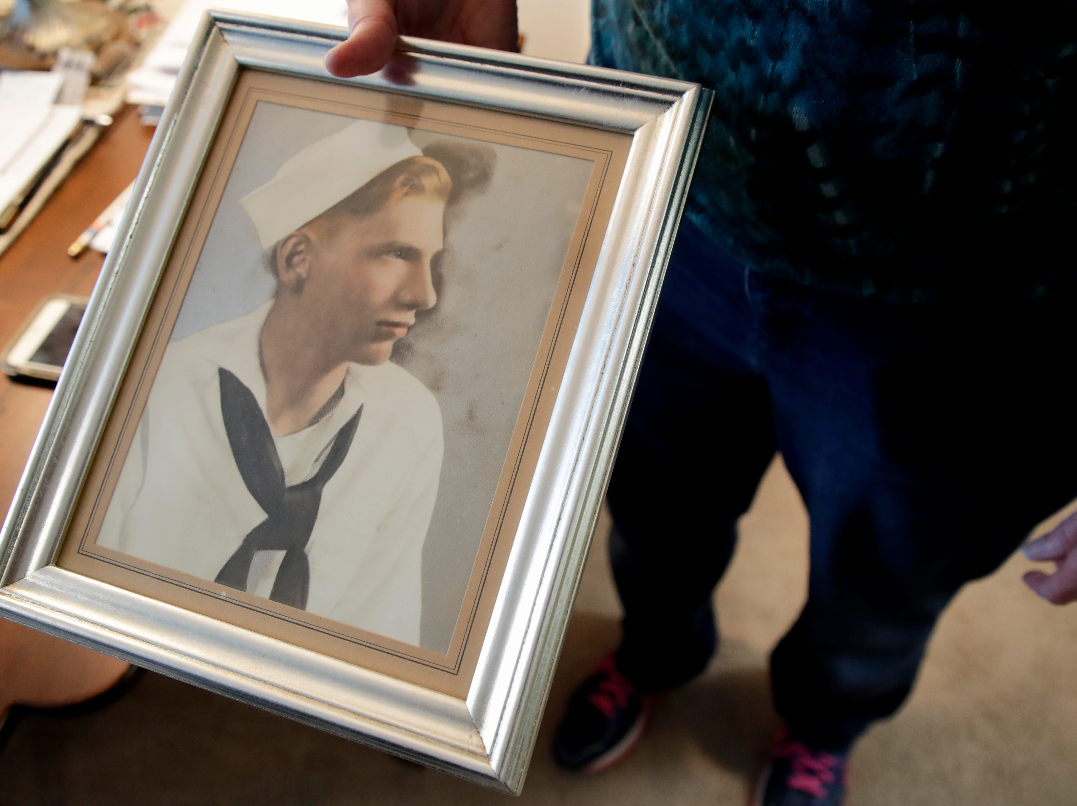 Sandy DeLopez holds a photo of the uncle she knew of her whole life but never met, Earl Baum, who died on the U.S.S. Oklahoma in Pearl Harbor December 7, 1941.