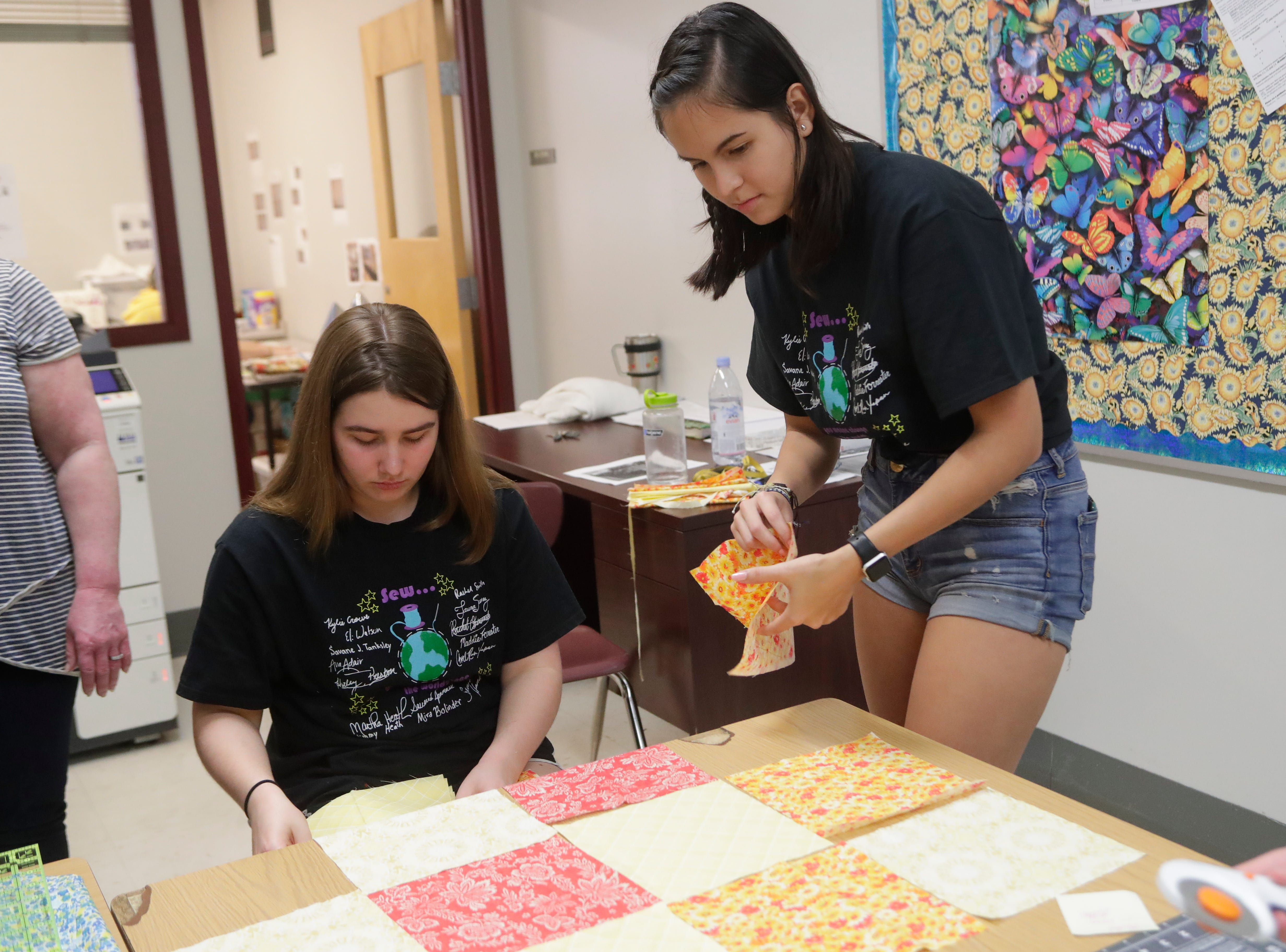 Rachel Ostrander, a senior at Chiles High School and member of the Chiles Sewing Club, left, and Laura Suarez, also a senior at Chiles High School, layout fabric squares as they prepare to make a quilt for people at Refuge House, Thursday Feb. 21, 2019.