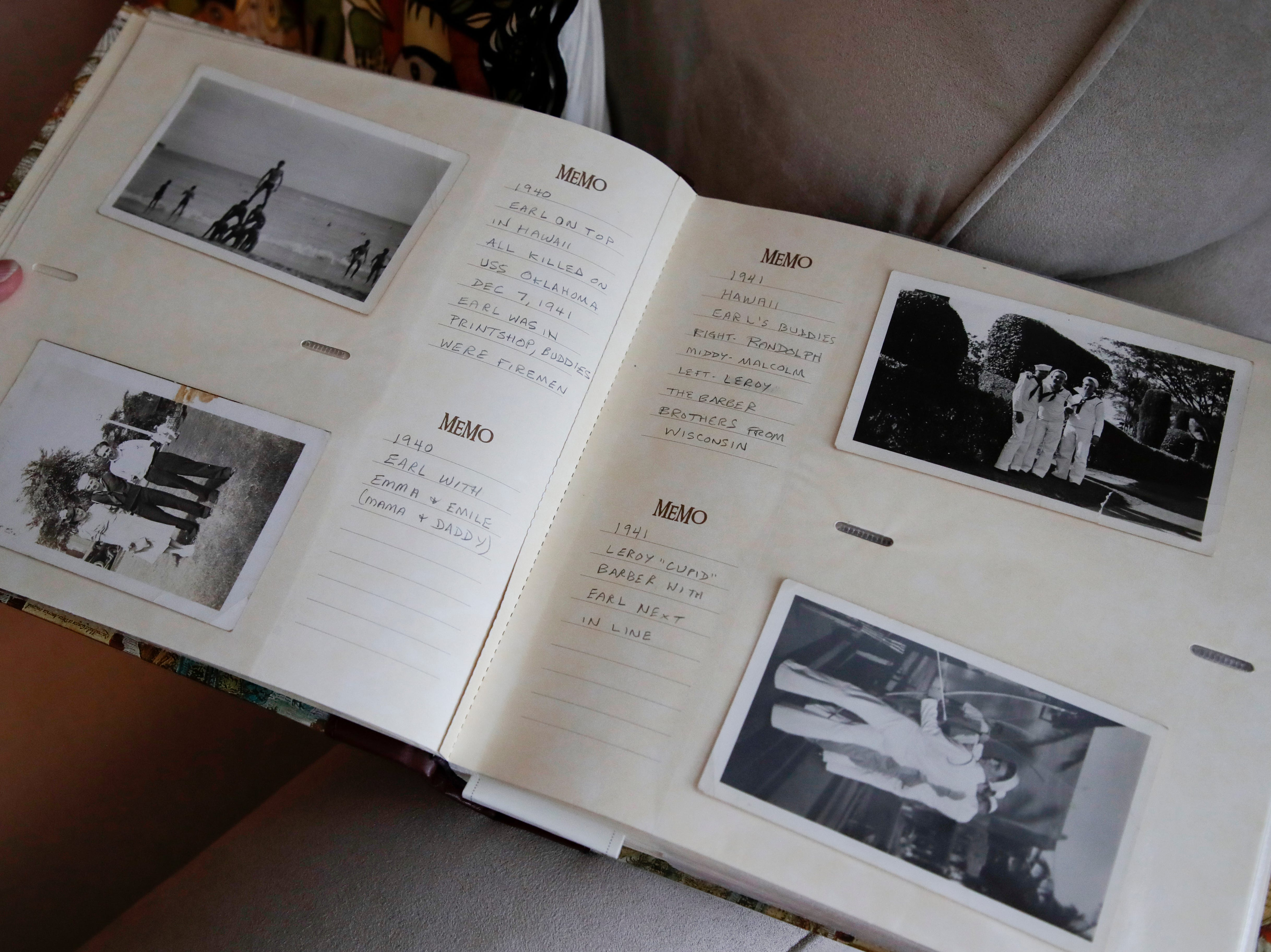 Sandy DeLopez holds a photo album that includes photos of her uncle Earl Baum before he died at Pearl Harbor Dec. 7, 1941.
