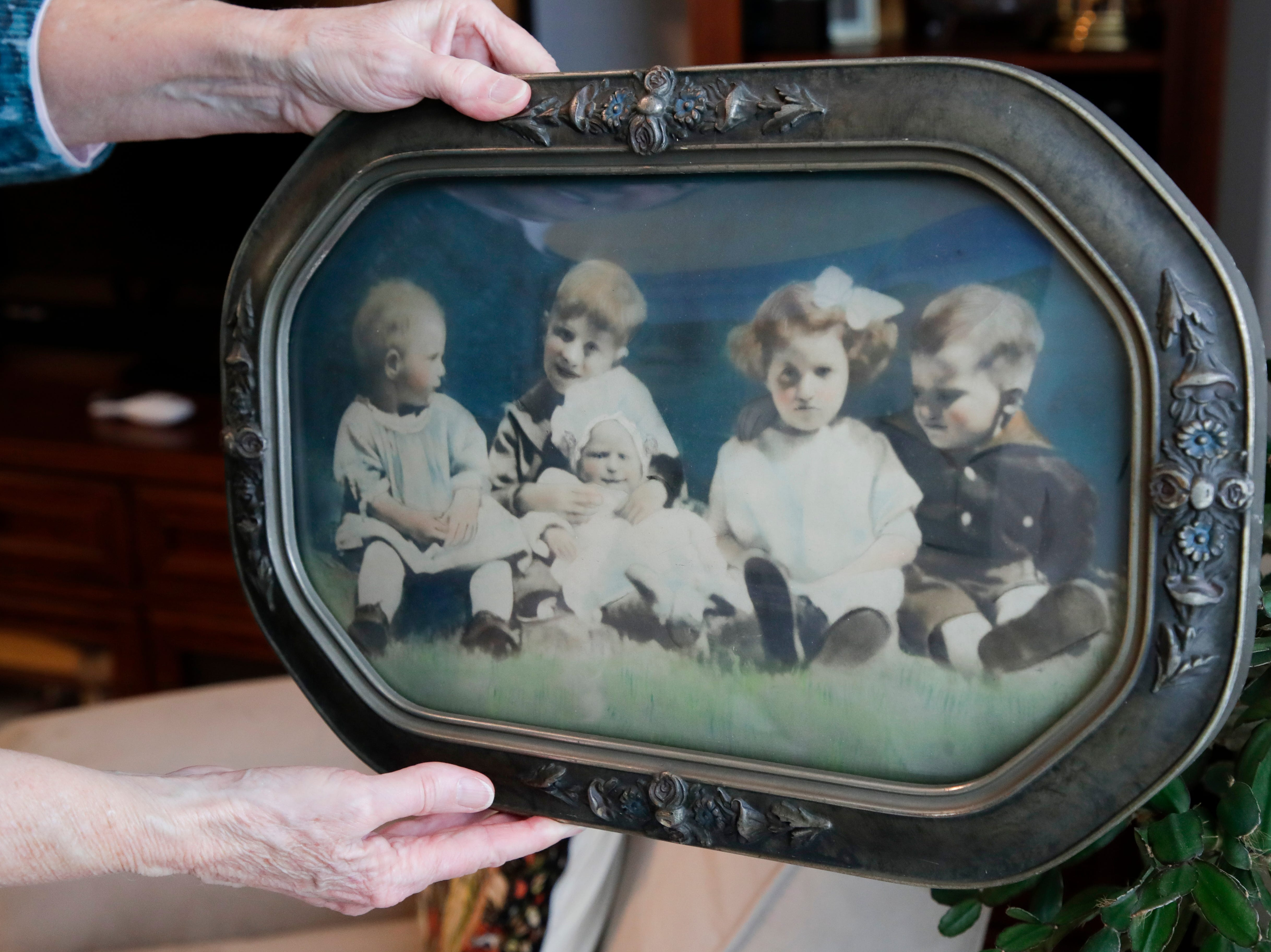 Sandy DeLopez holds a photo from her mother Emily Golz's childhood. The photo shows Golz, the youngest, being held in the lap of her oldest brother Earl Baum, who died at Pearl Harbor in 1941. Baum's remains were identified last year through DNA. He will be buried March 8, 2019 at Tallahassee National Cemetery.