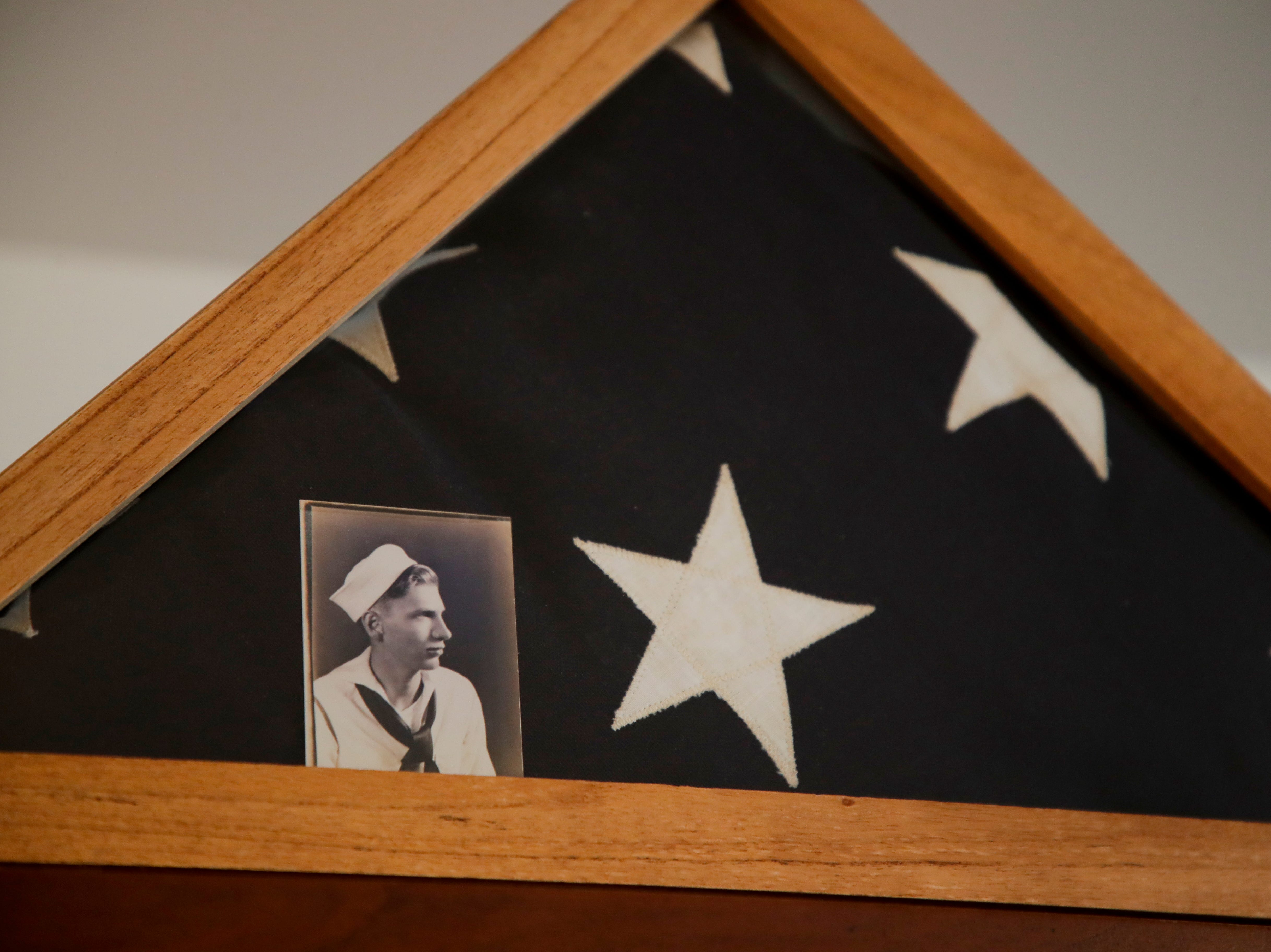 In the 90s, Emily Golz and family visited Arlington National Cemetery and received a flag for her brother Earl Baum, who died at Pearl Harbor in 1941. She keeps the flag and a photo of her brother in her home.