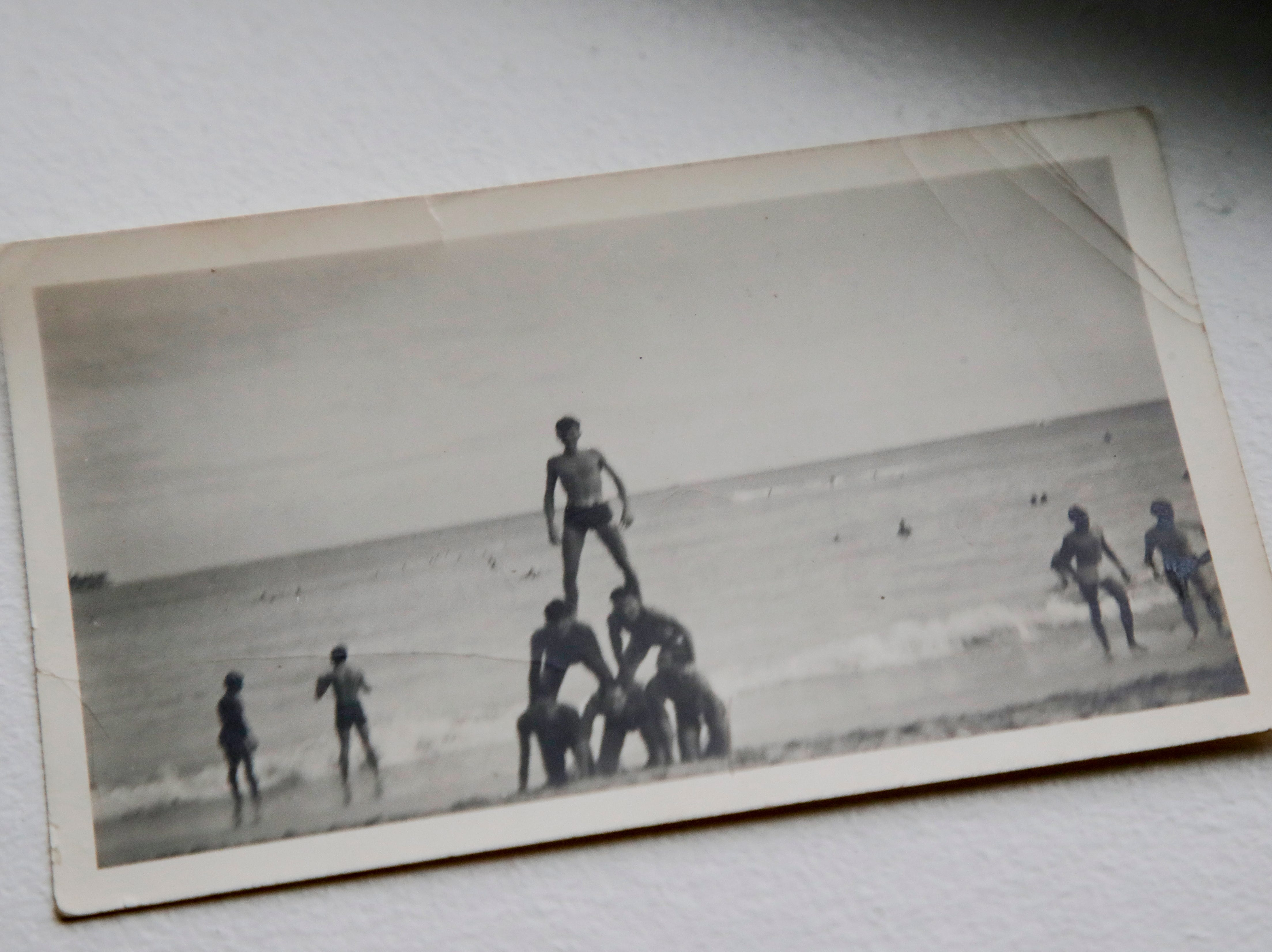 A photo shows Earl Baum on the top of a human pyramid at the beach before his death at Pearl Harbor Dec. 7, 1941.
