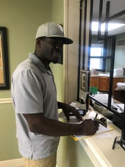 Texas contractor James Wilbon pays clerk at City Hall for water hookup for place where his workers are staying. He's been in Port St. Joe since two days after Hurricane Michael hit.