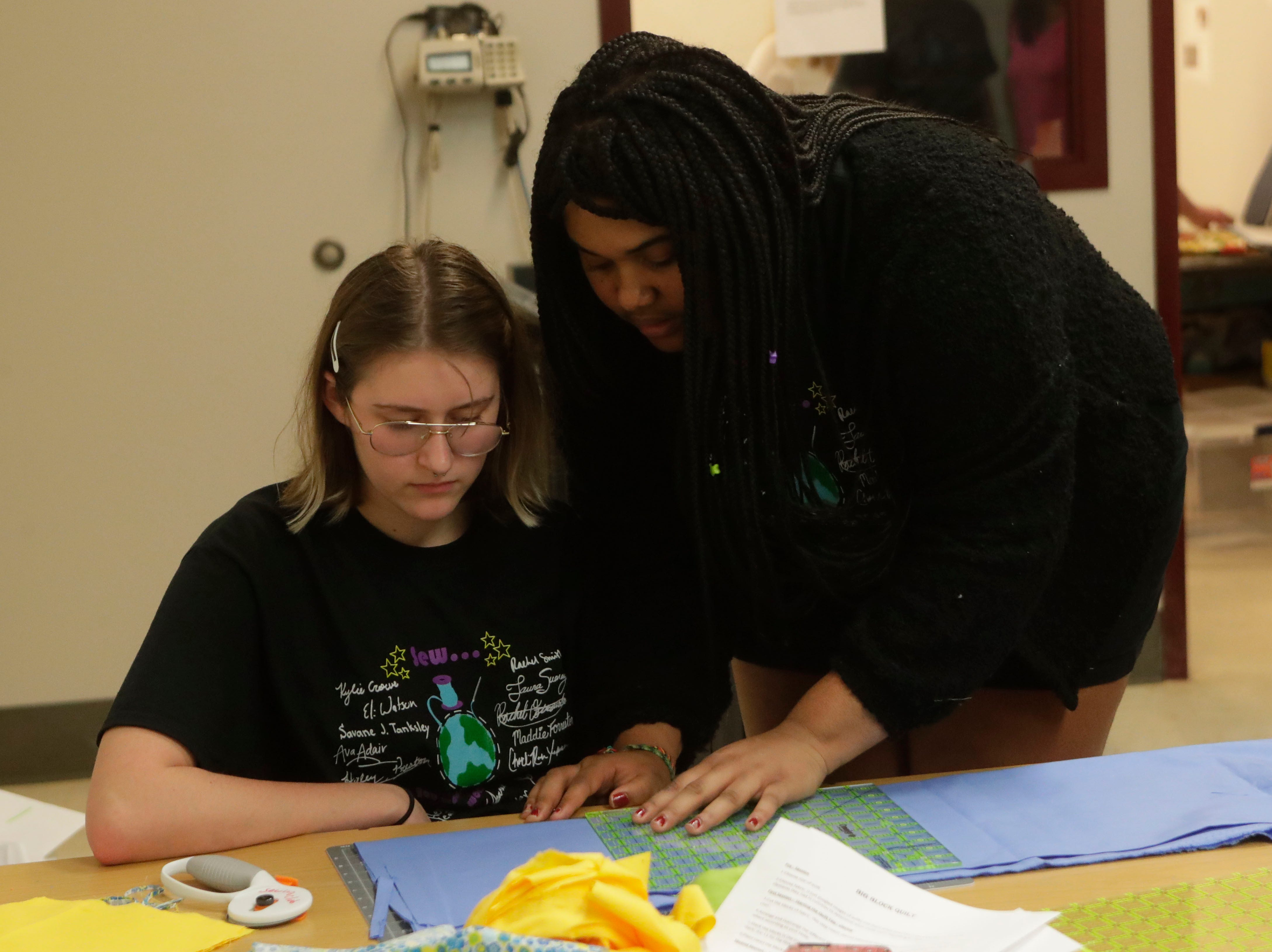 Mira Bolinder, a senior at Chiles High School and member of the Chiles Sewing Club, left, and Savannah Spannaus, president of the Chiles Sewing Club and a senior at Chiles High School, work together to measure squares of fabric which will be sewn into quilts for people at the refuge home, Thursday Feb. 21, 2019.