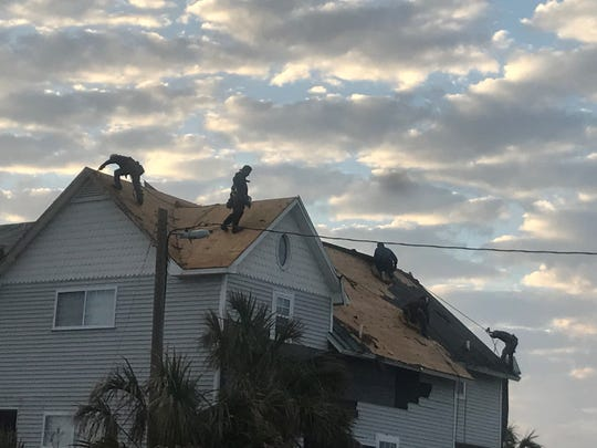 Laborers installing new roof on house at St. Joe Beach as the sun sets.
