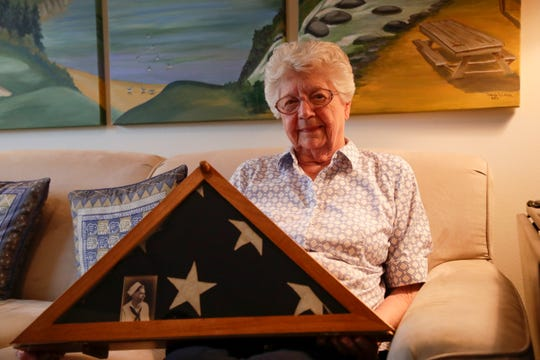 Emily Golz holds the flag she and her family received when they visited Arlington National Cemetery in the 90s for a ceremony recognizing her brother, Earl Baum, as missing in action from Pearl Harbor. She keeps the flag in her home.