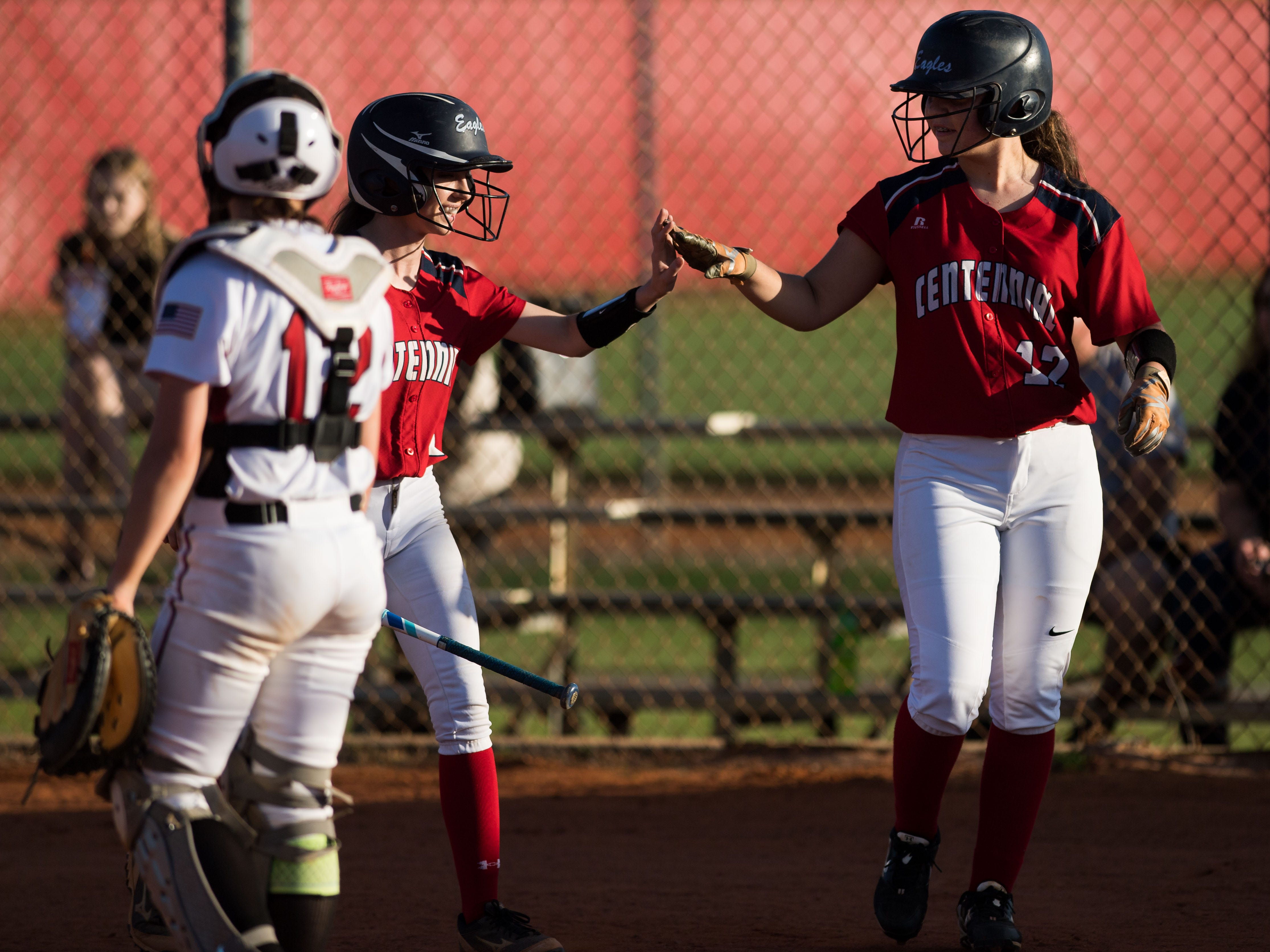 St. Lucie West Centennial's Vanessa Ordonez (right) is congratulated by teammate Rachel Thomas after scoring on a double hit by Randi Teed in the bottom of the fourth inning against Port St. Lucie during the high school softball game Wednesday, Feb. 20, 2019, at St. Lucie West Centennial High School in Port St. Lucie.