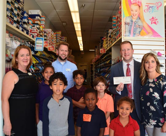 Jonathan Blackburn, divisional director at Senior Life Services, far right, presents a check to Cynthia Falardeau, far left, chief executive officer of the Education Foundation, at a recent Sneaker Exchange with Citrus Elementary School.