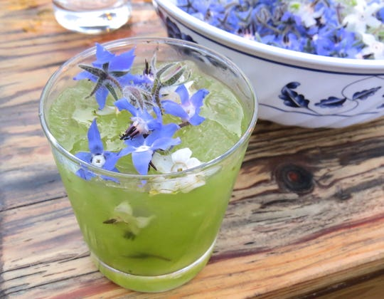 An arugula gimlet made with CBD oil and topped with blue and white borage blooms by mixologist Matthew Biancaniello is seen at a dinner in Ojai.
