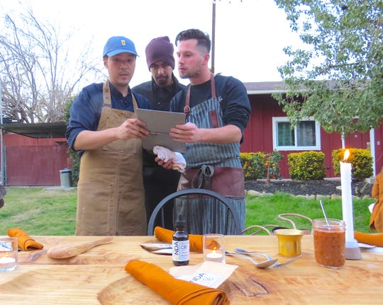 Chefs Ryan Simorangkir, left, Omar Uribe, center, and Tyler Peek discuss the placement of dishes during a CBD-themed dinner in Ojai.