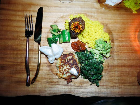"""Food made with, and without, CBD oil is displayed on a """"plate"""" carved into the communal Family Supper Plank table used during a recent dinner in Ojai."""
