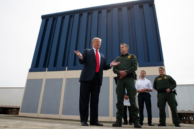 In this March 13, 2018, file photo, President Donald Trump talks with reporters as he reviews border wall prototypes in San Diego.