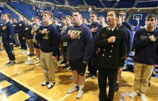 Thomas Ott of Lewes (center) sings the Navy anthem with his teammates after competing against American in his last home wrestling match in Annapolis. Ott overcame family trauma to gain entrance to the US Naval Academy and is now poised to graduate.