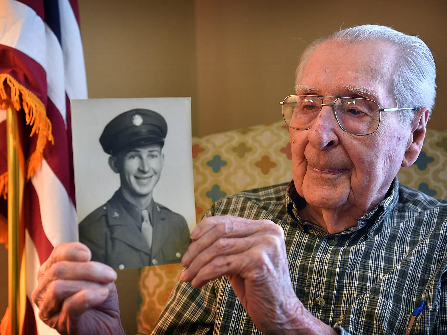 Joe Cuba holds a photograph of himself taken early in his military service in the U.S. Army Air Corps in World War II. Cuba will turn 100-years old on March 2.