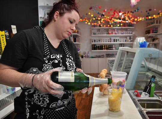 Brenna Pohlod, owner of Clink!, pours champagne over alcohol-infused pineapple sorbet and fresh fruit while making an adult dessert named White Girl Brunch. Pohlod opened her adult dessert bar in mid February.