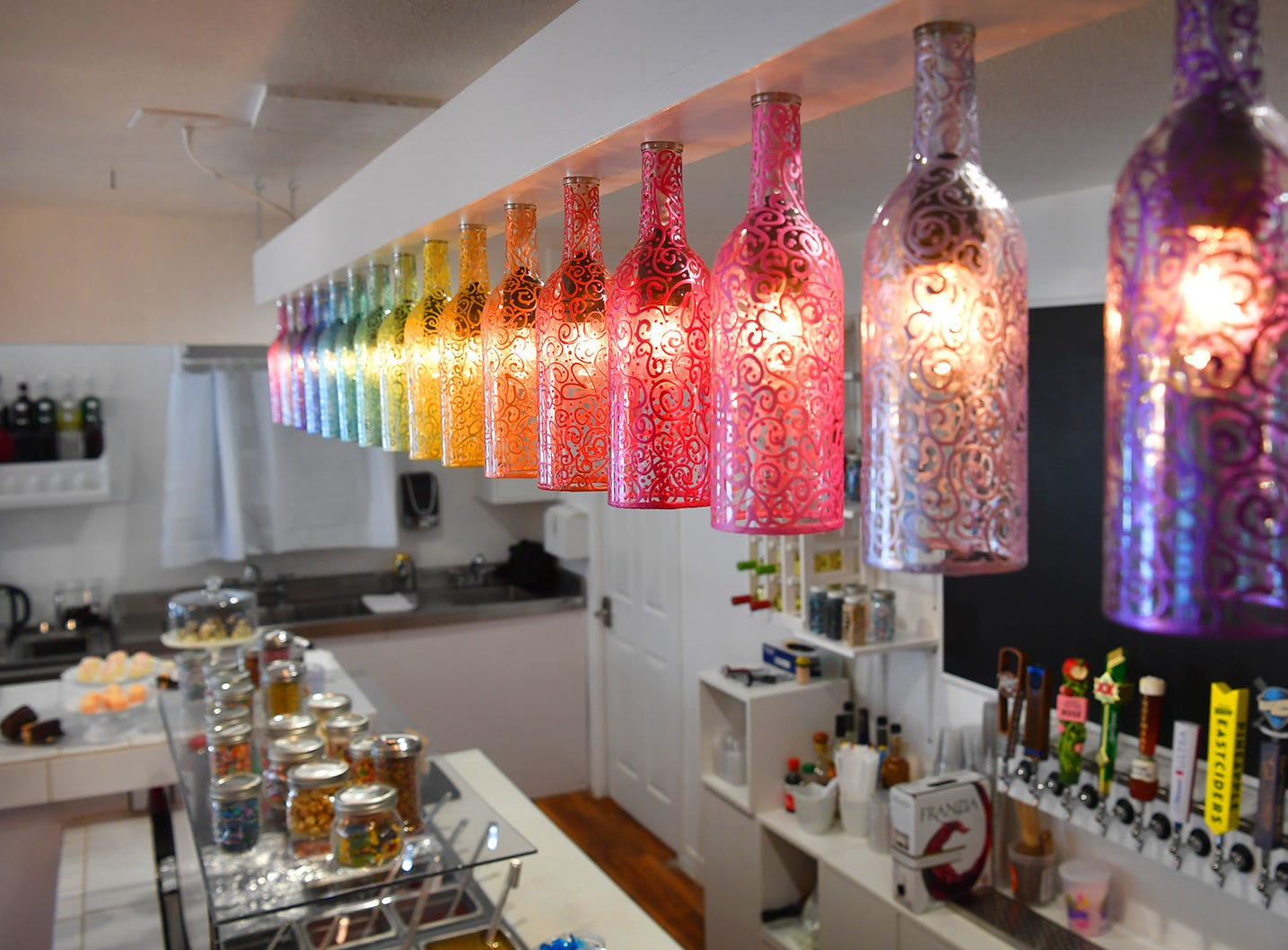 Hand-painted wine bottles make up many of the light fixtures in Clink!, a new adult dessert bar located on Kemp Blvd. The light and colorful decor was designed by the owner, Brenna Pohlod.