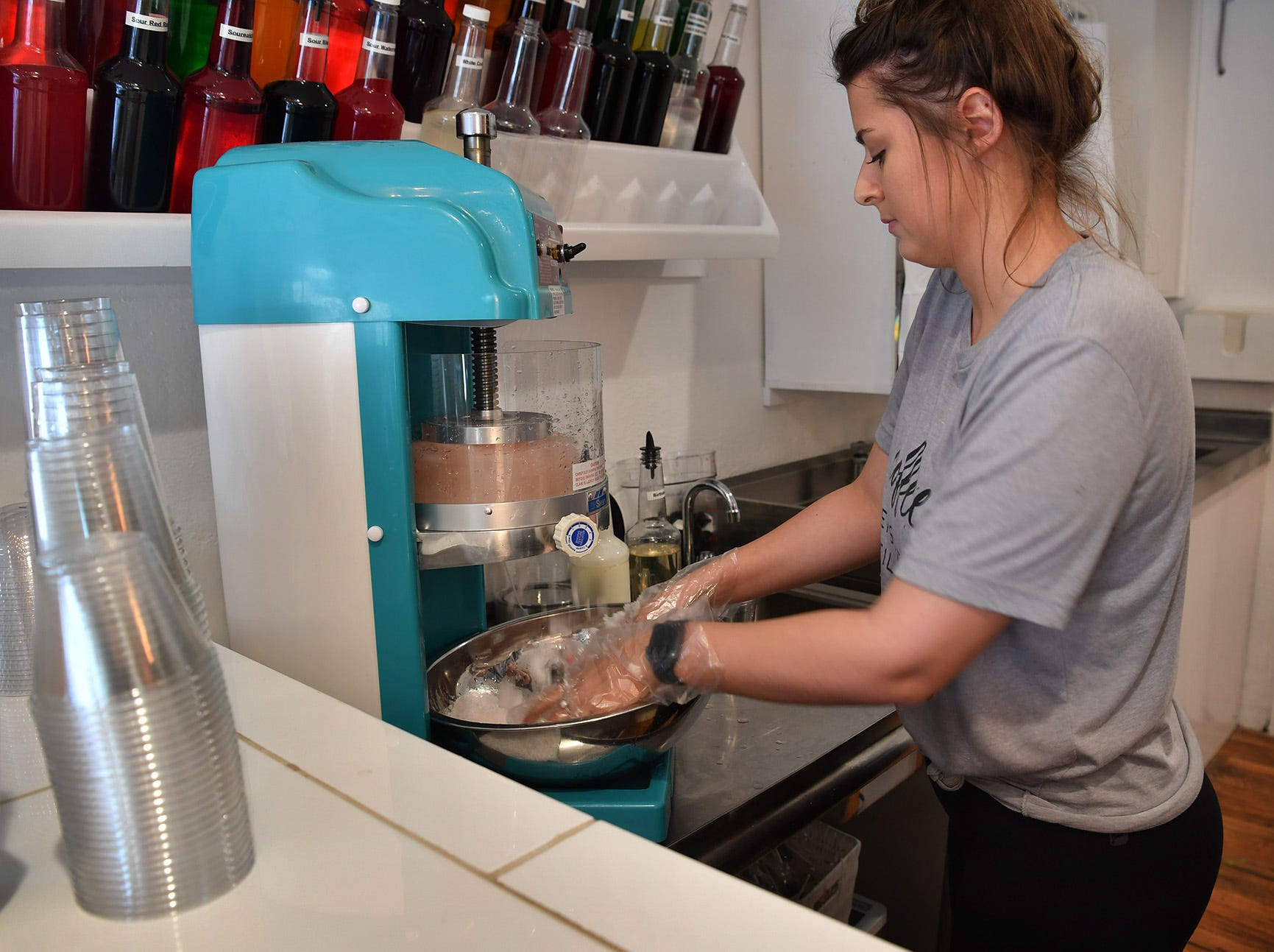 Lauren Givens, assistant manager of Clink!, an adult dessert bar, makes a snow cone with shaved frozen wine. The new business also offers alcohol-infused fruits, cupcakes and ice creams.
