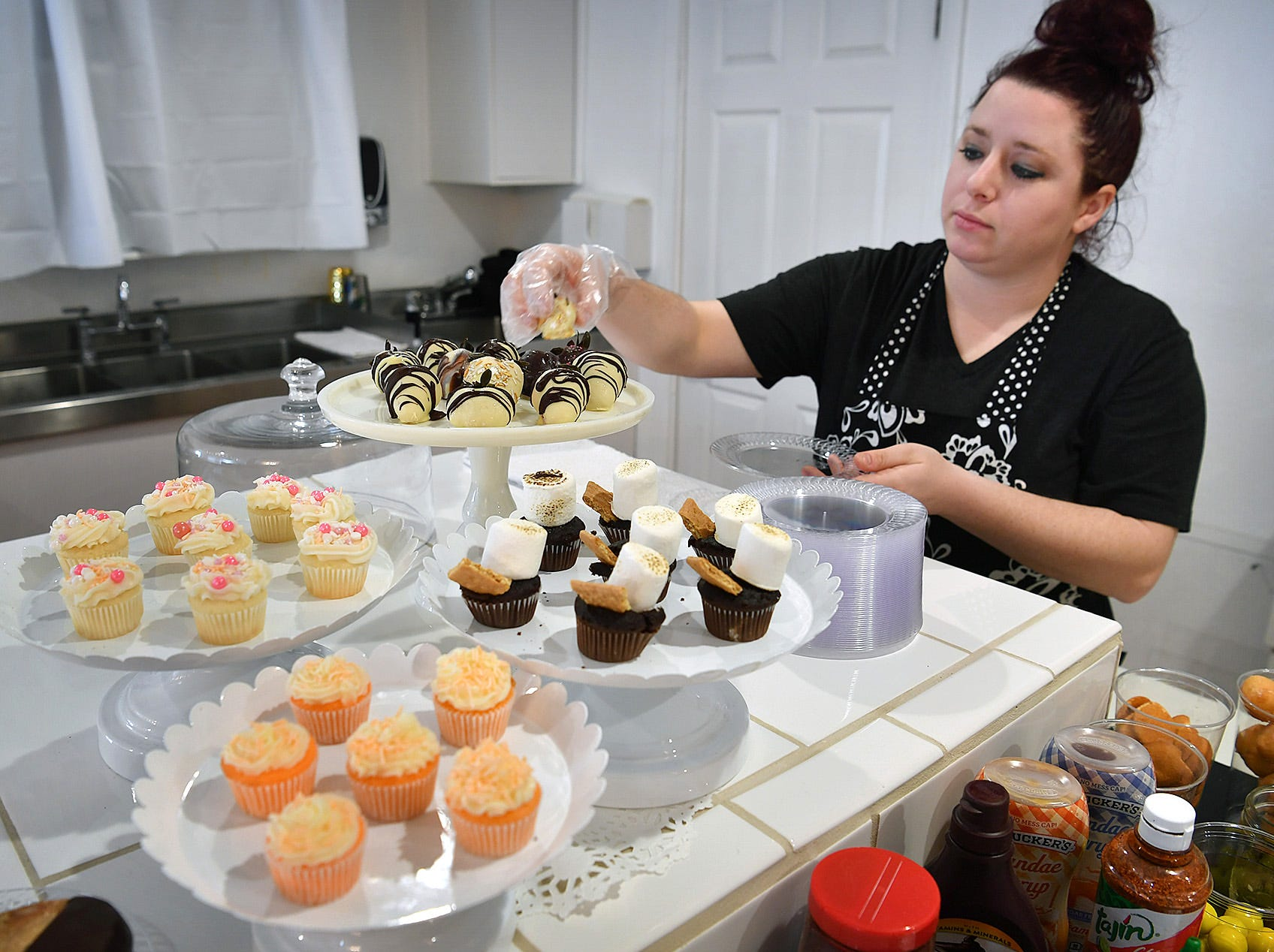 Brenna Pohlod adds to a display of alchohol-infused strawberries and cupcakes at her new business, Clink!, an adult dessert bar. They also offer ice creams, sherbets, sorbets, candy and fresh fruit made with alcohol.