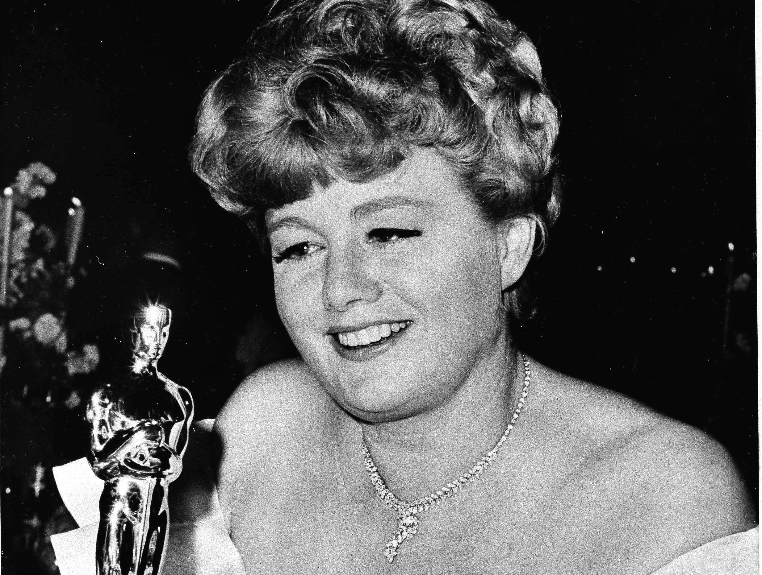 """U.S. actress Shelley Winters, whose role in """"A Patch of Blue"""" won her the 'Best Supporting Actress' Oscar at last night's Academy Awards, admires the Golden Statuette at an Academy party, Santa Monica, CA, April. 19, 1966."""