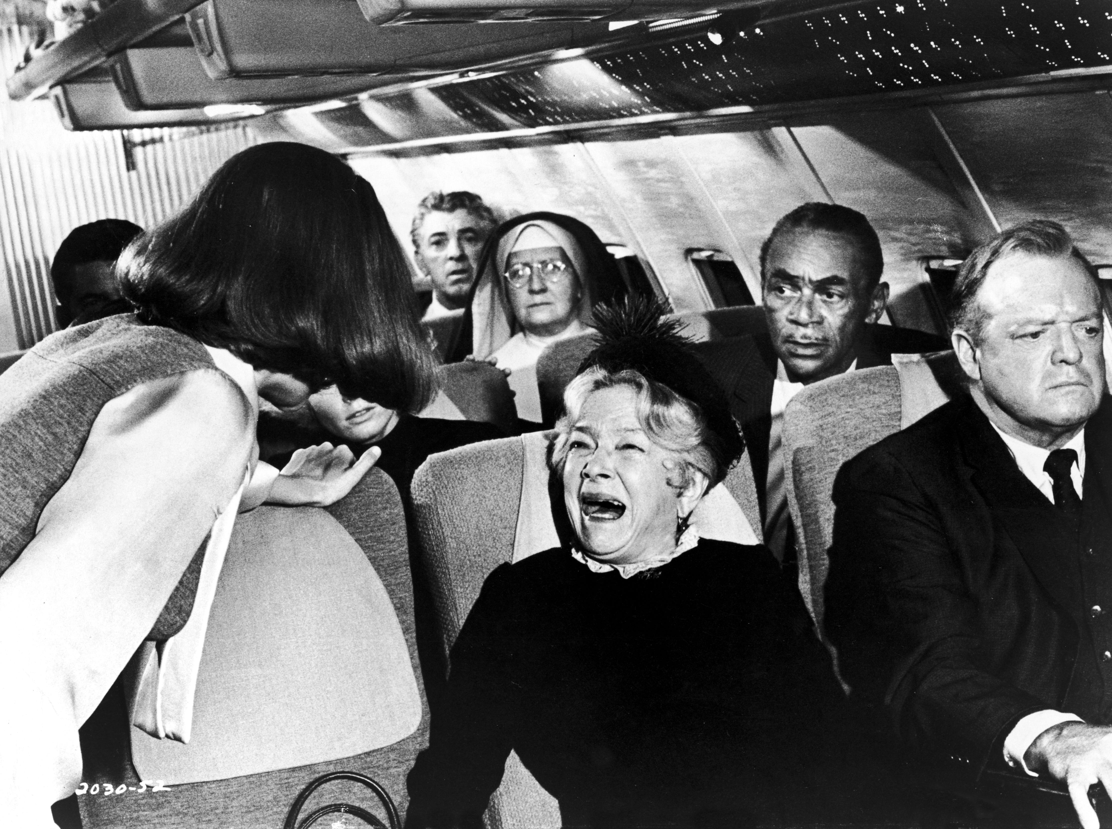 ONE TIME USE 2/21/2019 American actor Helen Hayes (1900 - 1993) cries hysterically as a flight attendant attempts to calm her and American actor Van Heflin (1910 - 1971) looks away in a still from the film, 'Airport,'  directed by George Seaton.