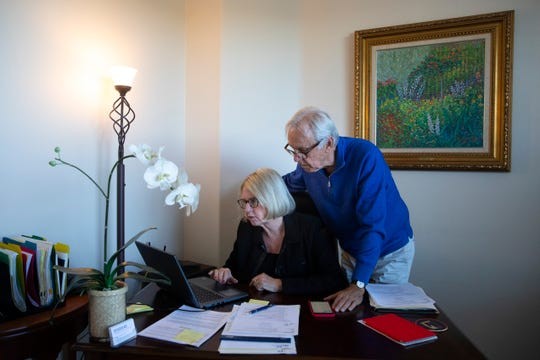 Debbie Douglas works on her computer as her husband and business partner, Gary, watches in their home office in Newport Beach, Calif., on Feb. 6, 2019.