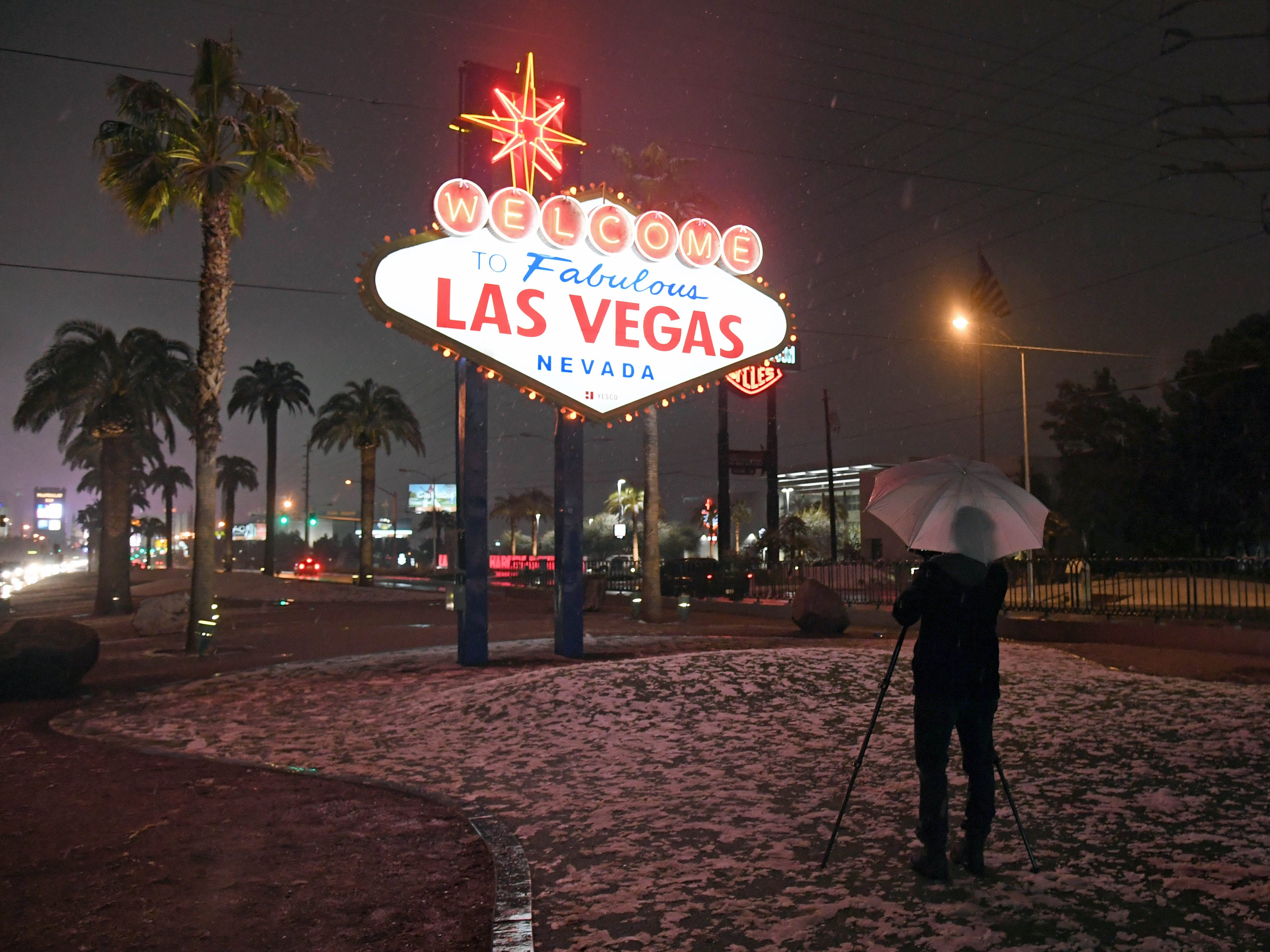 """A photographer uses an umbrella to protect his camera from snow at the """"Welcome to Fabulous Las Vegas"""" sign on Feb. 20, 2019."""