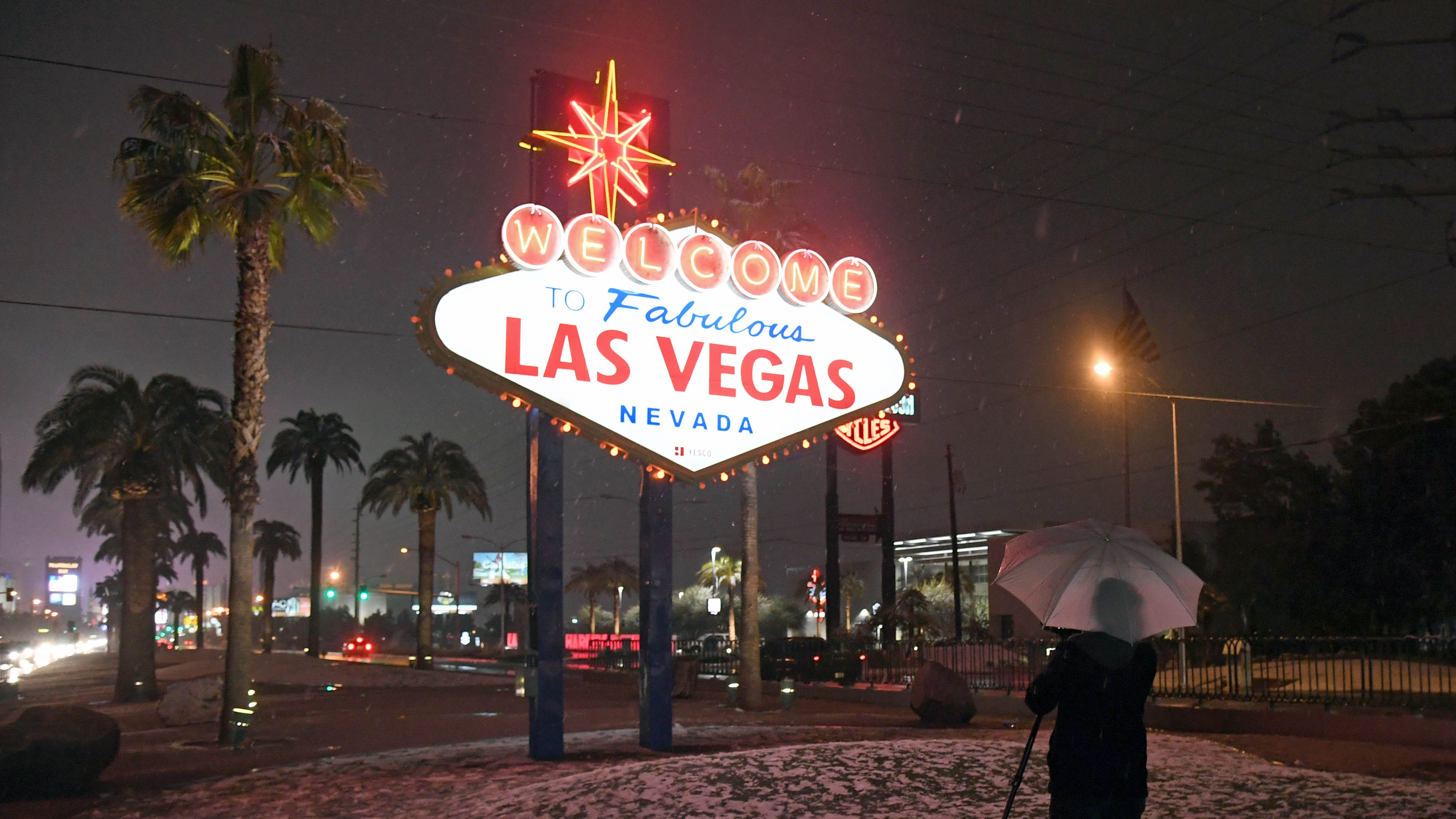 "A photographer uses an umbrella to protect his camera from snow at the ""Welcome to Fabulous Las Vegas"" sign on Feb. 20, 2019."
