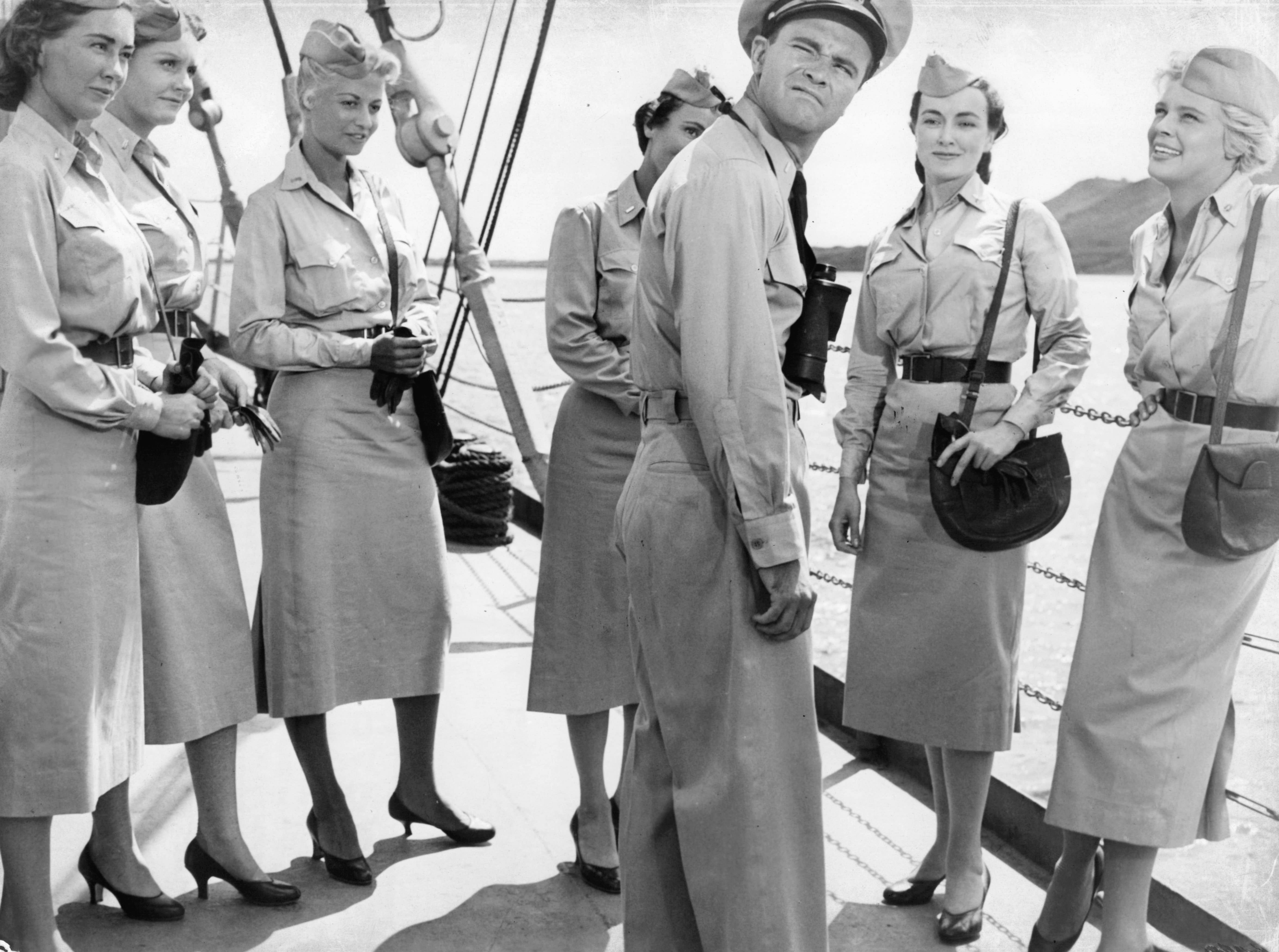 ONE TIME USE 2/21/2019 Jack Lemmon is standing in the center of six unknown actresses aboard a military ship, who are staring at him as he looks away in a scene from the film 'Mister Roberts', 1955. (Photo by Warner Brothers/Getty Images)