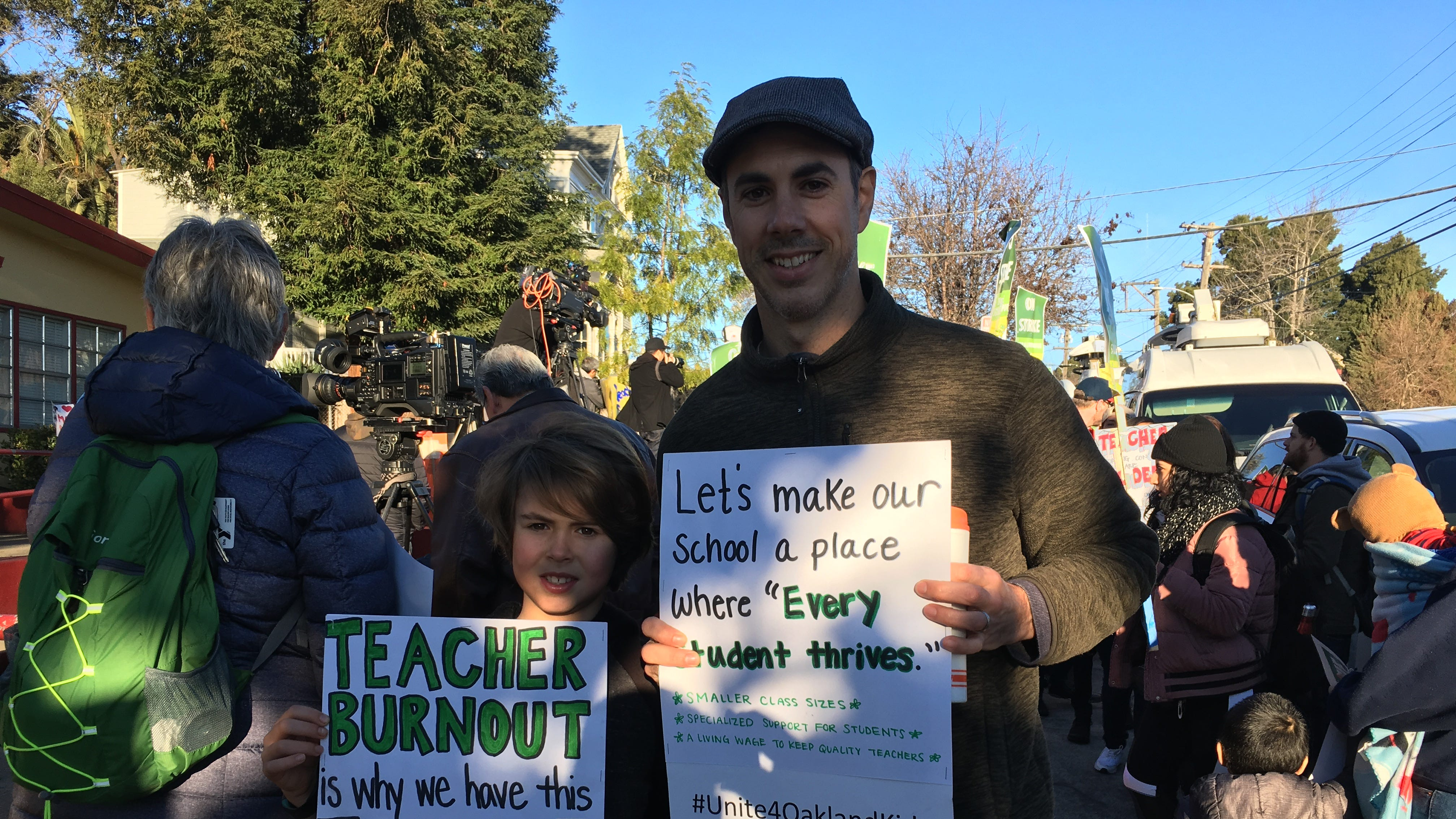 Patrick Vaughn and his son Whitworth, a third grader , rally in Oakland, Calif., on Feb. 21, 2019.