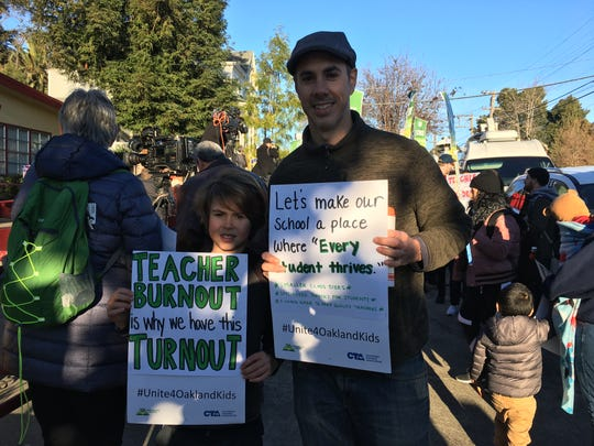 Patrick Vaughn and his son Whitworth, a third-grader, rally in Oakland, Calif., on Feb. 21, 2019.