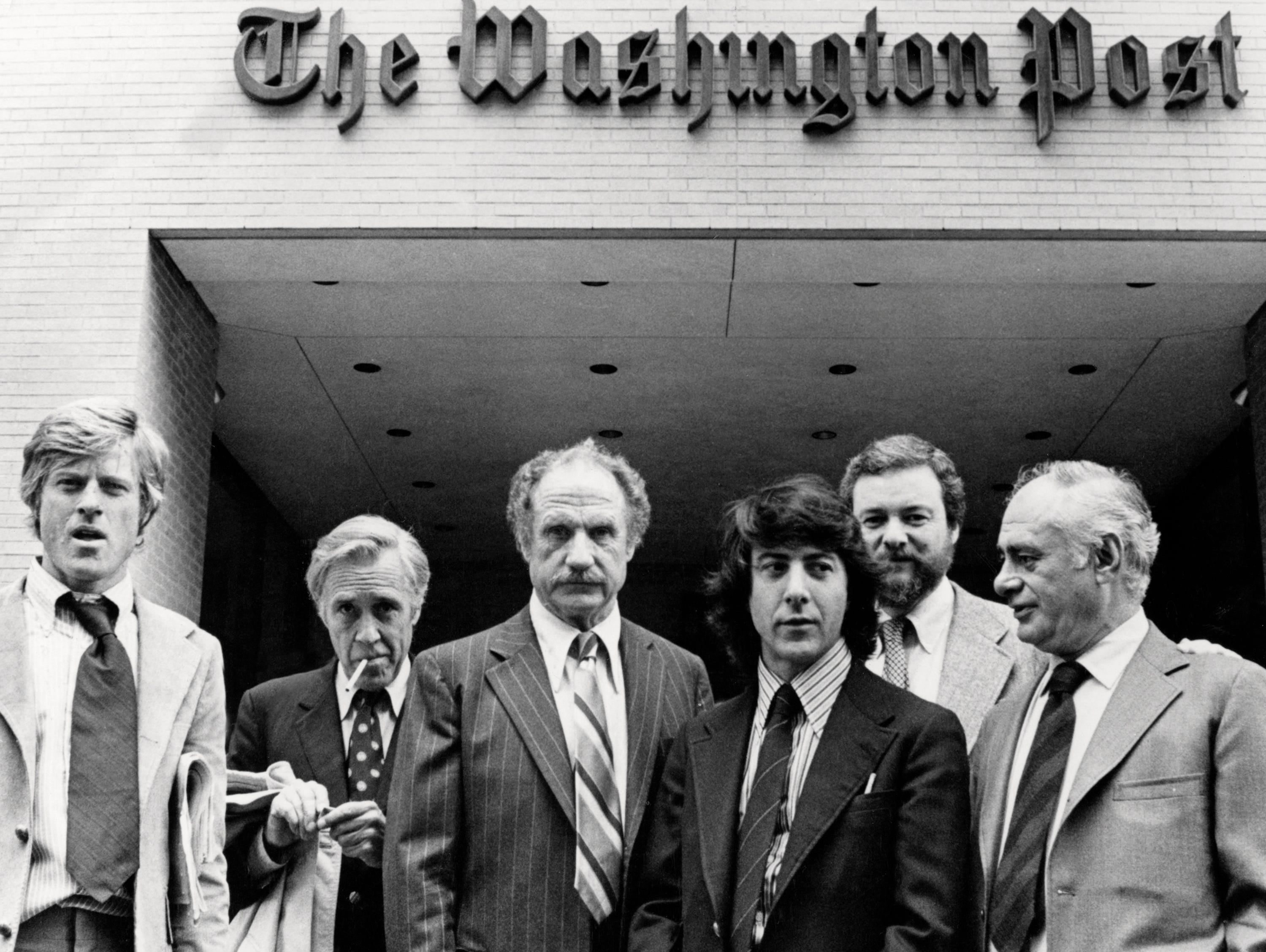 The director and cast members of 'All The President's Men' outside the offices of the Washington Post, 1976. Left to right: Robert Redford (who plays Bob Woodward in the film), Jason Robards (1922 - 2000, plays Ben Bradlee), Jack Warden (1920 - 2006, plays Harry Rosenfeld), Dustin Hoffman (plays Carl Bernstein), director Alan J. Pakula (1928 - 1998) and Martin Balsam (1919 - 1996, plays Howard Simons).