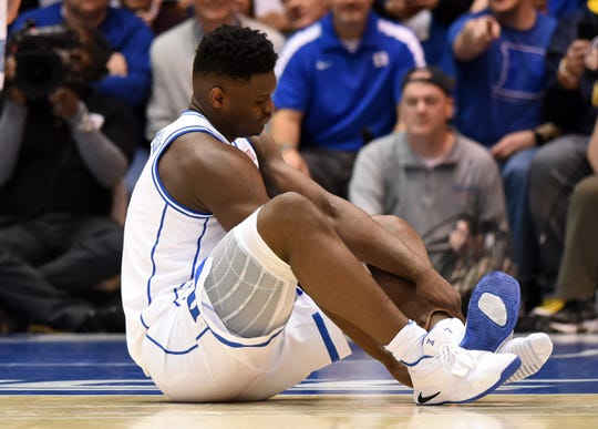 Duke forward Zion Williamson reacts after injuring his knee against North Carolina.