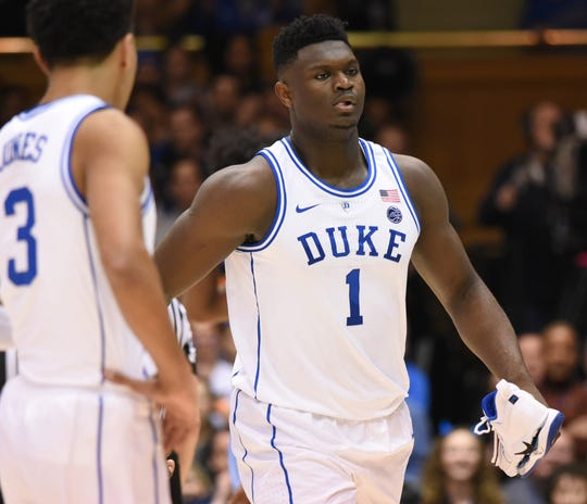 Zion Williamson walks off the court while holding his broken shoe.