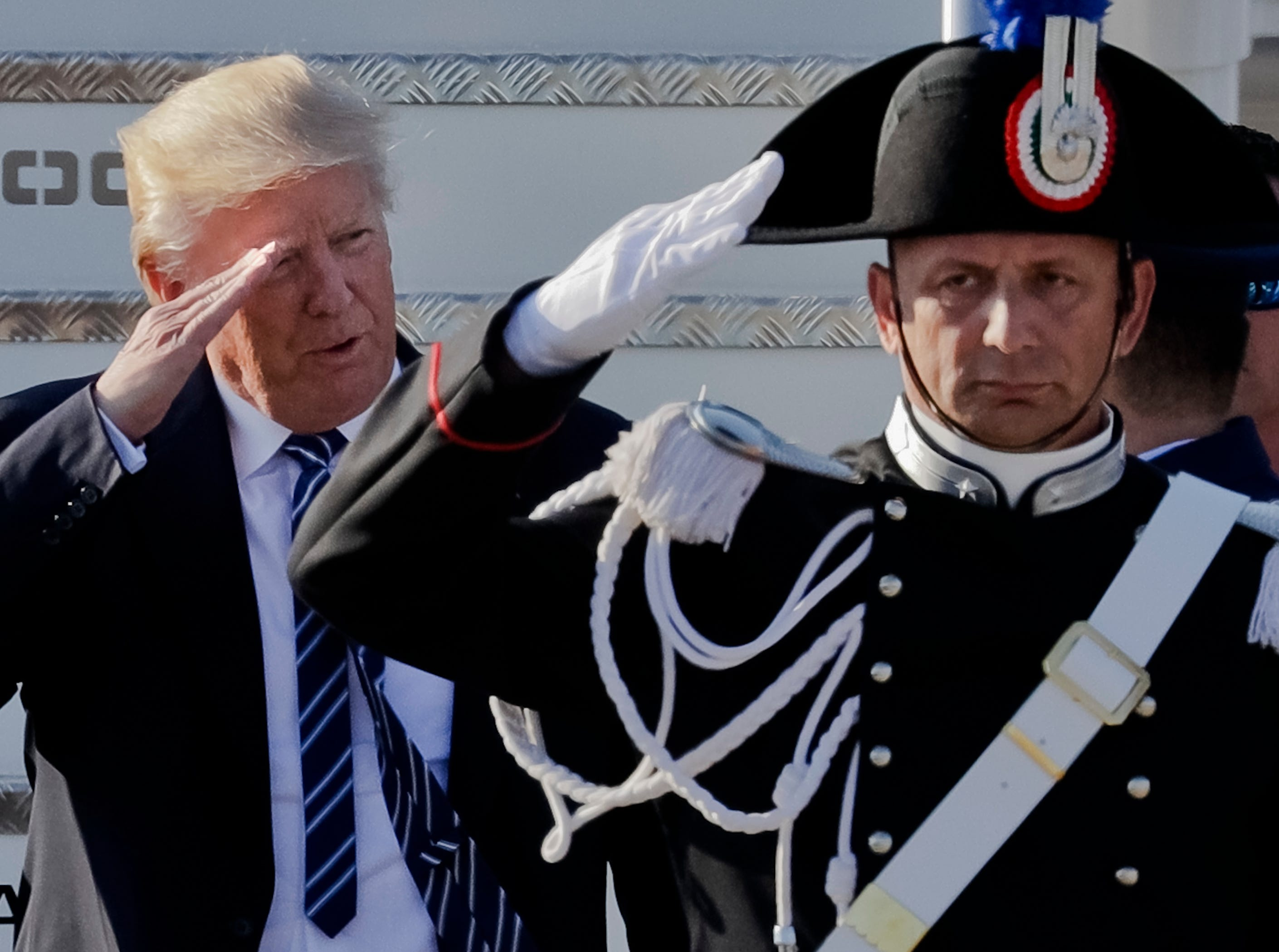 President Trump salutes a Carabinieri paramilitary officer upon his arrival at Fiumicino's Leonardo Da Vinci International airport, near Rome on May 23, 2017.