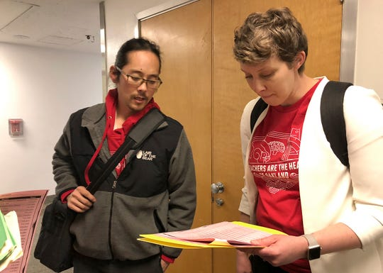 Cliff Hong, a principal at Roosevelt Middle School, left, and Amie Lamontagne, a principal at Fred T. Korematsu Discovery Academy, discuss their schedule for meeting with California lawmakers about Oakland school funding during a visit to the Capitol in Sacramento, Calif., Wednesday, Feb. 20, 2019.