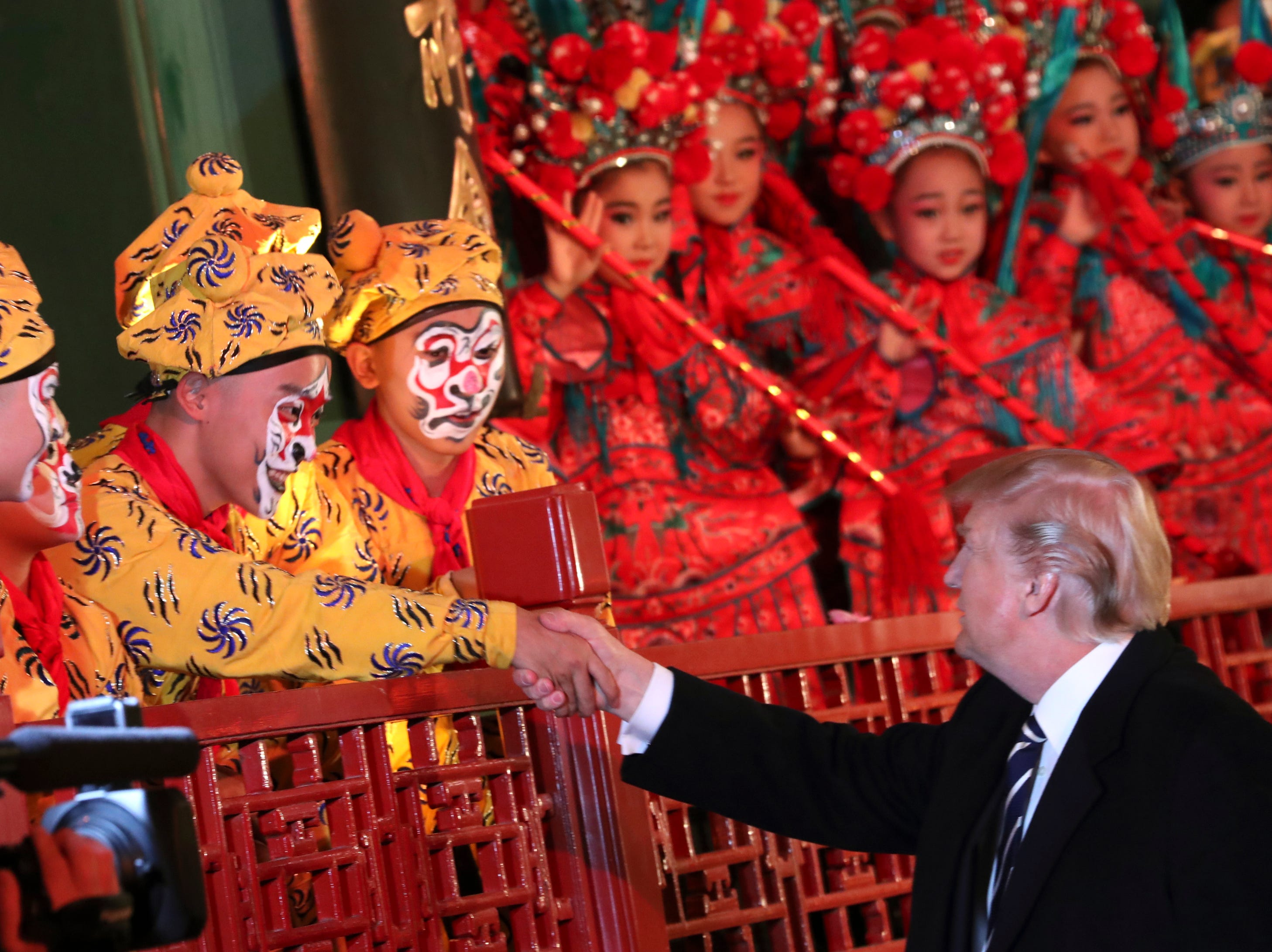 President Trump shakes hands with an opera performer at the Forbidden City, on Nov. 8, 2017, in Beijing, China.