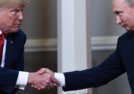 President Donald Trump, left, and Russian President Vladimir Putin shake hands at their meeting in Helsinki on July 16, 2018.