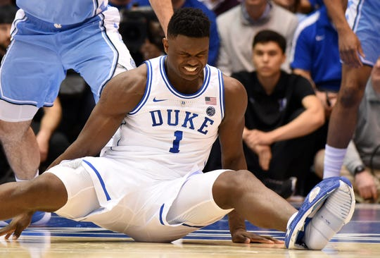 Duke Blue Devils forward Zion Williamson  reacts after his shoe gave way during a game against North Carolina.