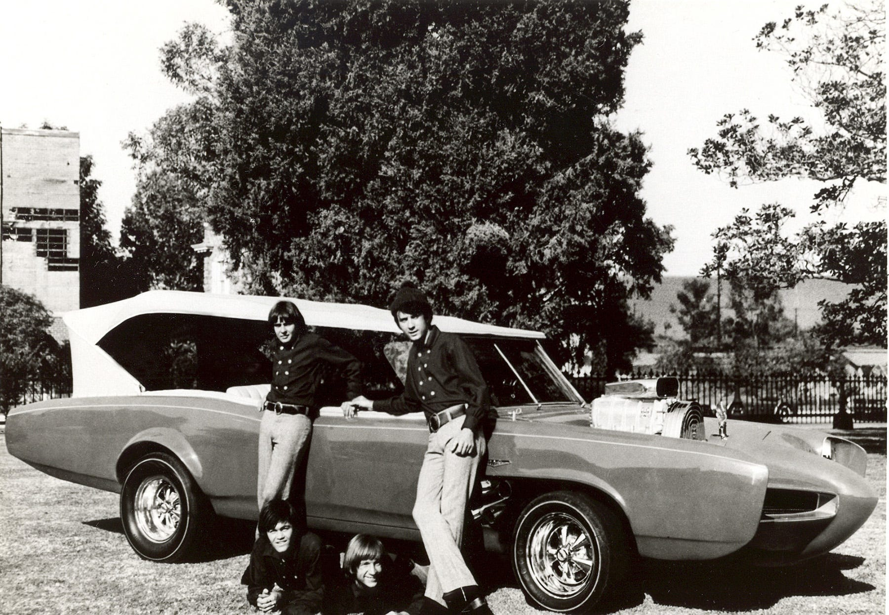 """In this 1966 file photo, cast members of the television show """"The Monkees,"""" from top left, Davy Jones, Michael Nesmith, from lower left, Micky Dolenz, and Peter Tork pose next to their customized Pontiac GTO."""