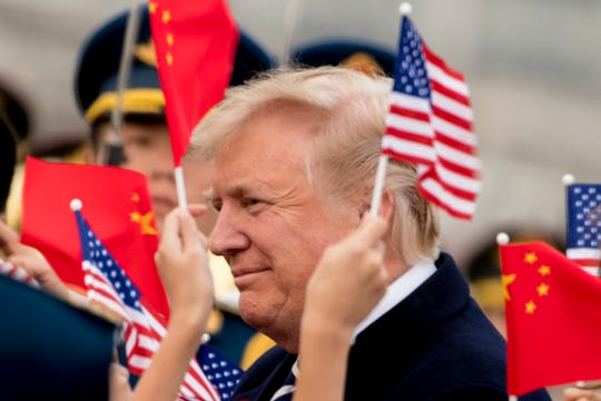 Children wave U.S. and Chinese flags as President Trump arrives at the Beijing Airport, in Beijing, China on Nov. 8, 2017.