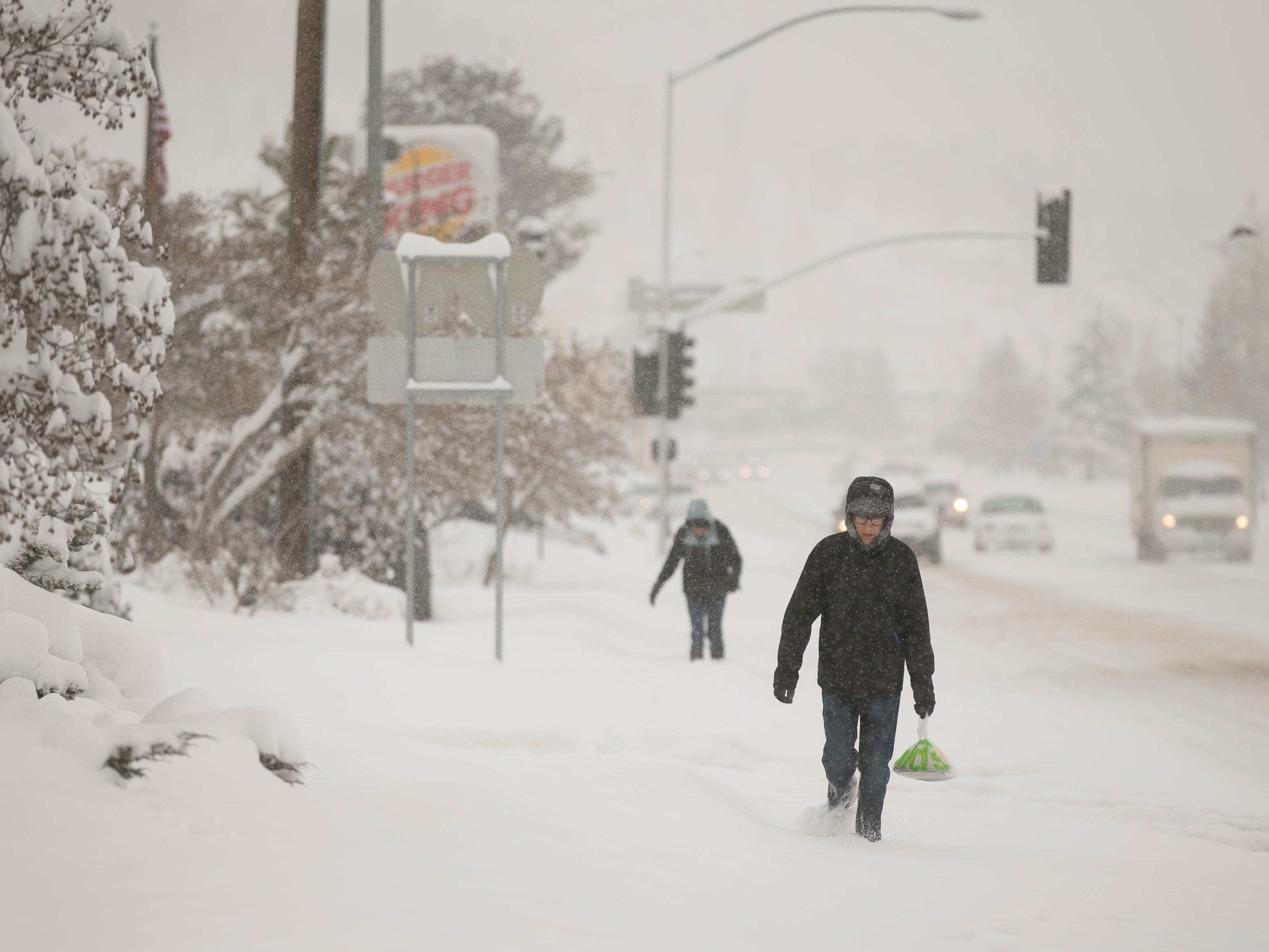 Northern Arizona University student Matthew Bartush carries breakfast through the snow as it falls over Flagstaff,  Feb. 21, 2019. This storm was expected to bring 20-30 inches of snow around northern Arizona through Friday.