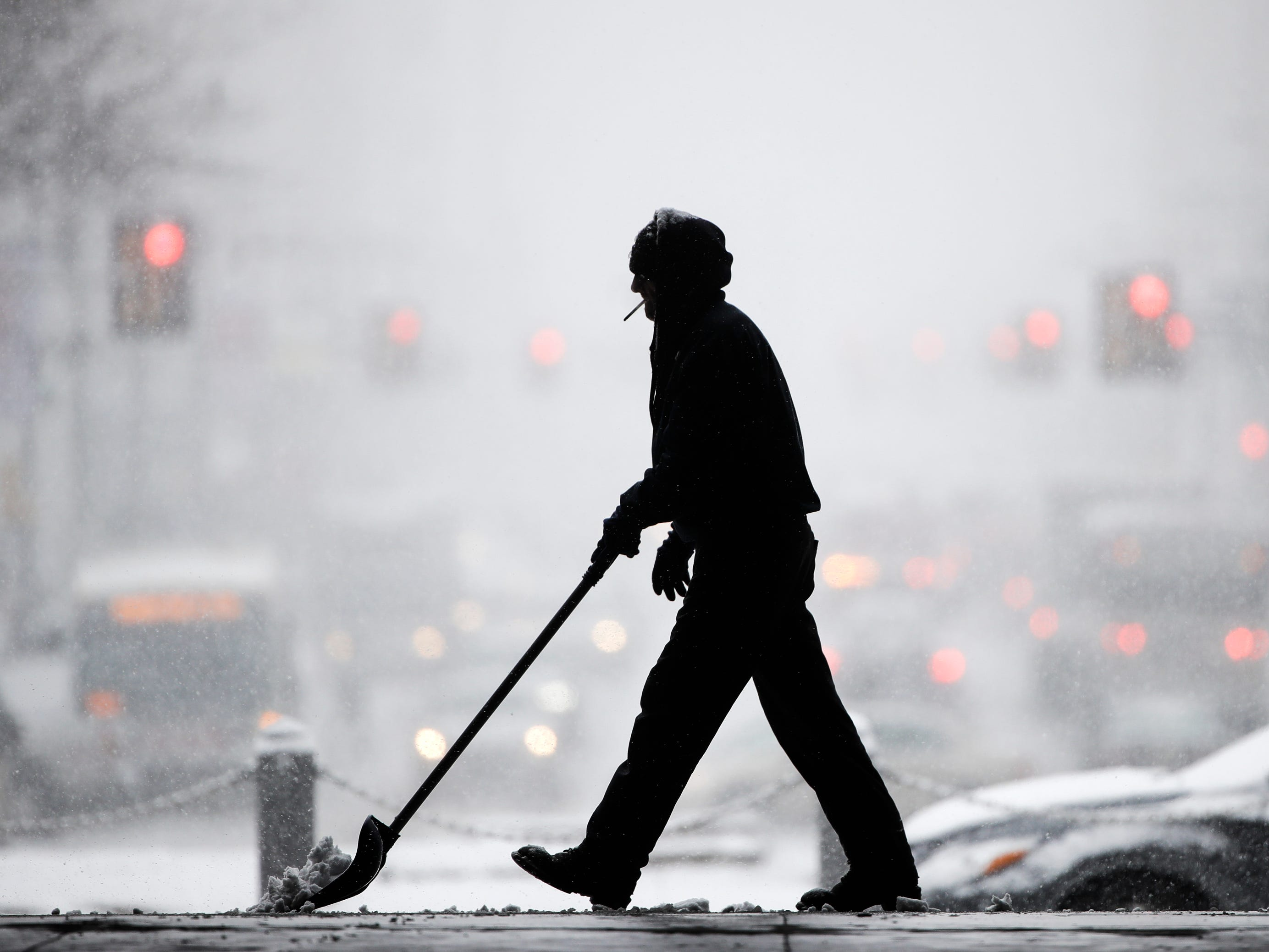 A worker at City Hall shovels snow during a winter storm in Philadelphia on Feb. 20, 2019.