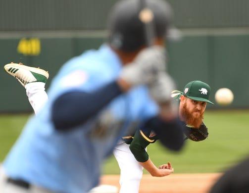 Feb. 21: Athletics pitcher Paul Blackburn delivers to Mariners outfielder Domingo Santana.