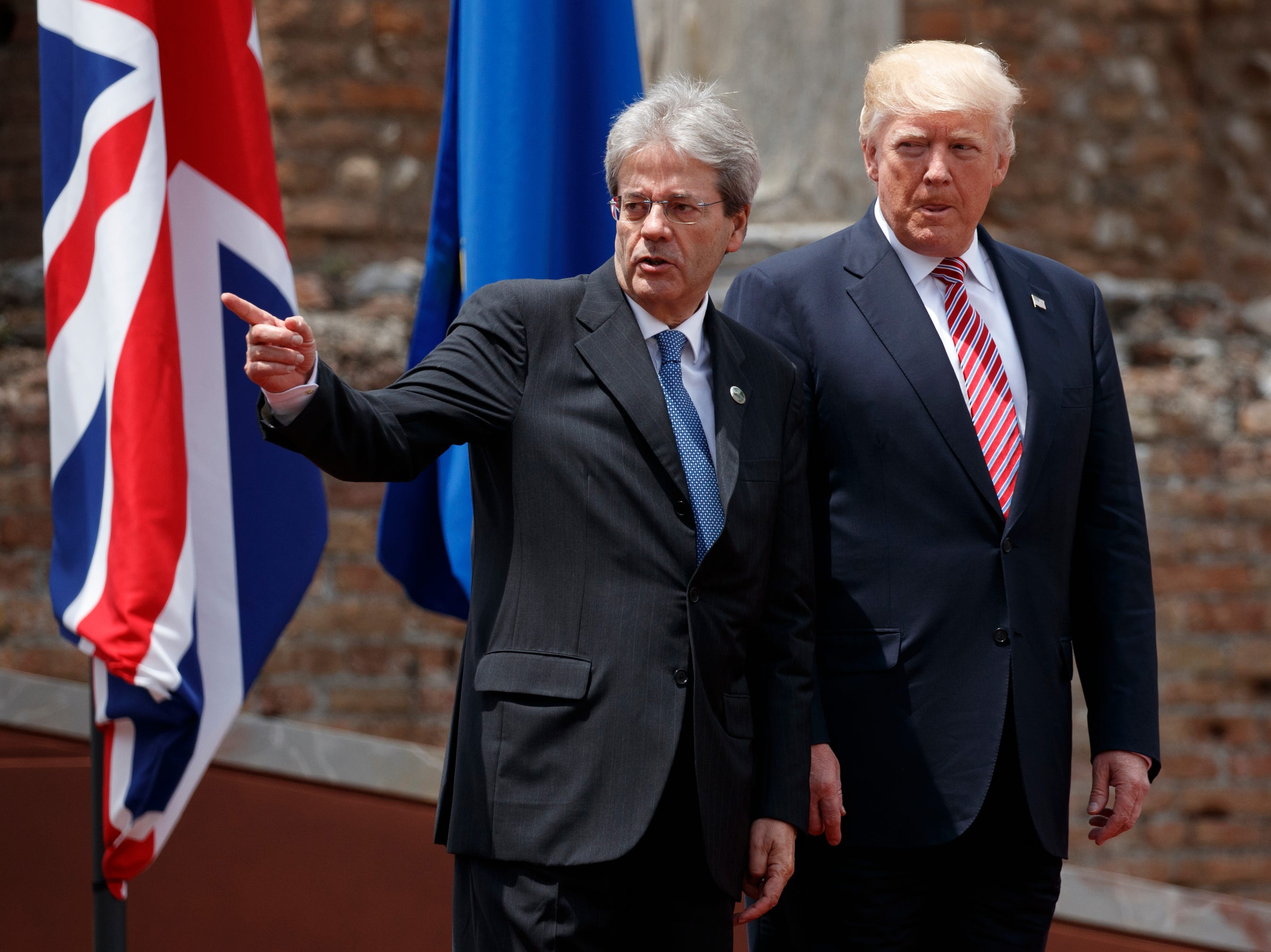 President Trump walks with Italian Prime Minister Paolo Gentiloni after arriving for a family photo with G7 leaders at the Ancient Greek Theater of Taormina on May 26, 2017, in Taormina, Italy.